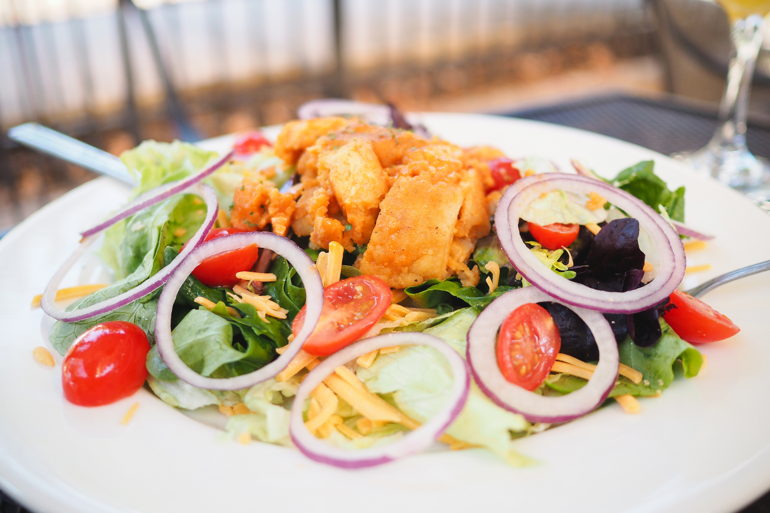 Lake Lawsona Spicy Chicken: Mixed lettuce topped with tender spicy strips of chicken, red onion, cheddar and tomatoes.