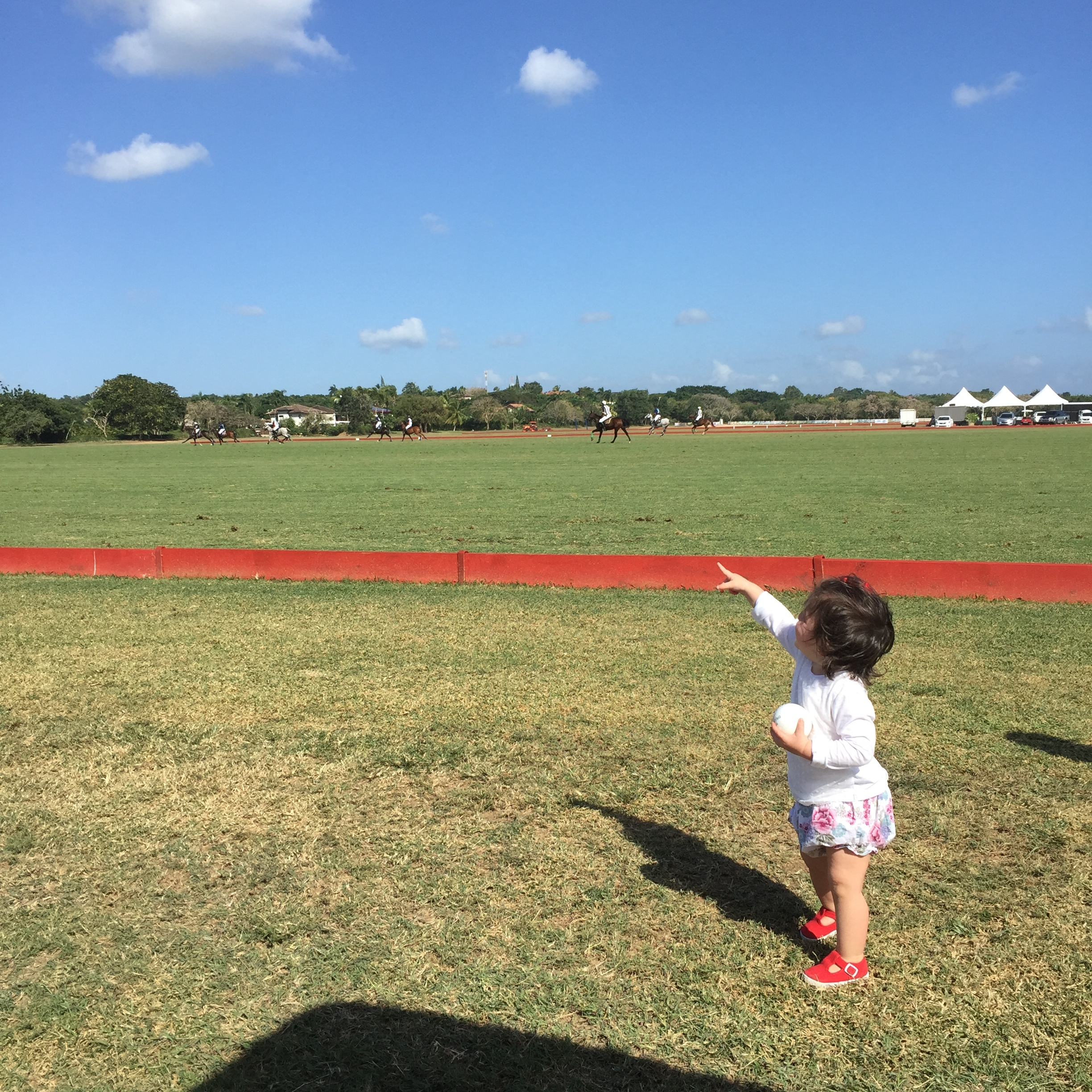 """Polo has come a long way at Casa de Campo. It was such a treat and very exciting to get to check out high goal polo while visiting. Such a beautiful setting and easily accessible to the public. Make sure to check it out if you are in CDC this season. She is fascinated by all things in the sky, in this case the """"Polo Drone""""."""