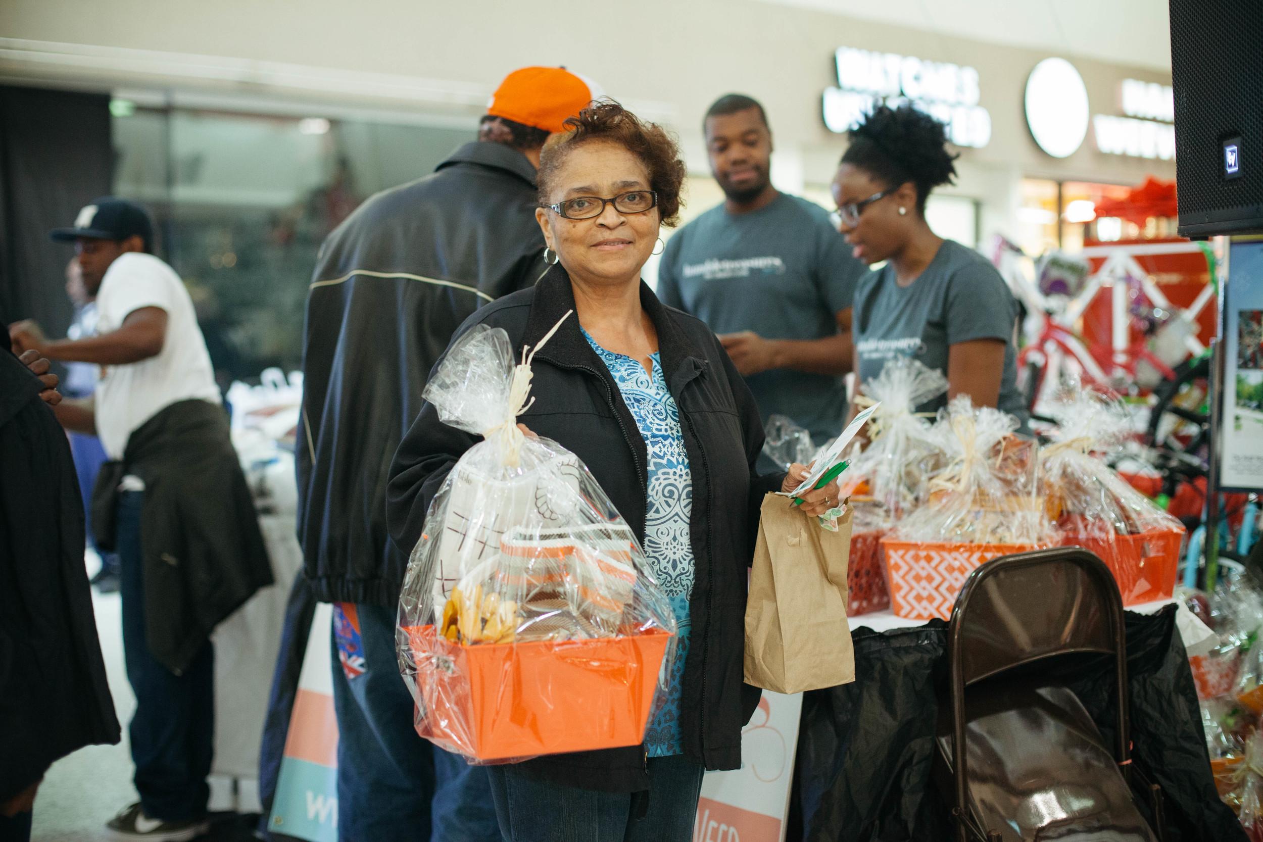 Woman receives basket at Thanksgiving Turkey Bash