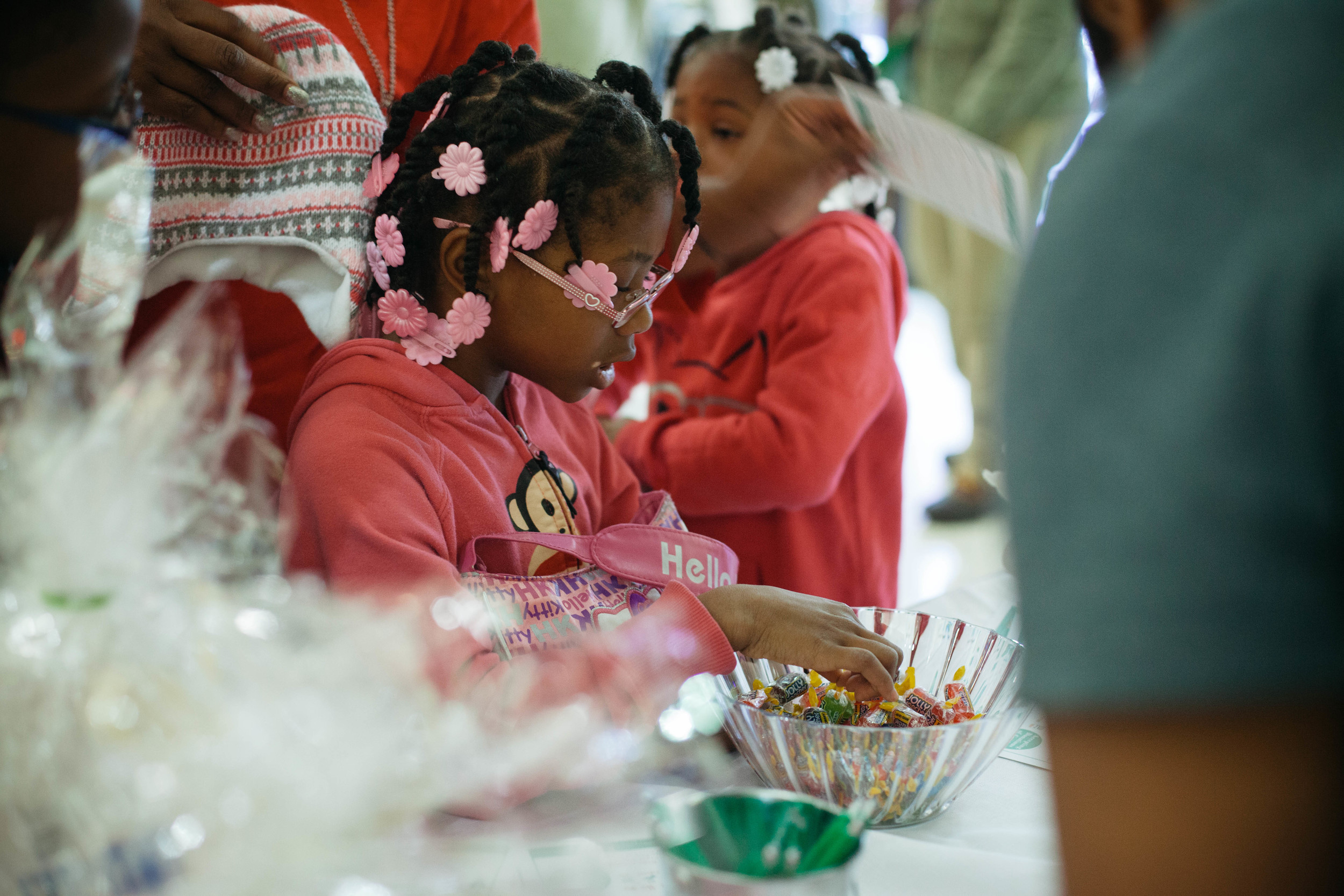 Girl looks through candy bowl at Humble Treasures booth
