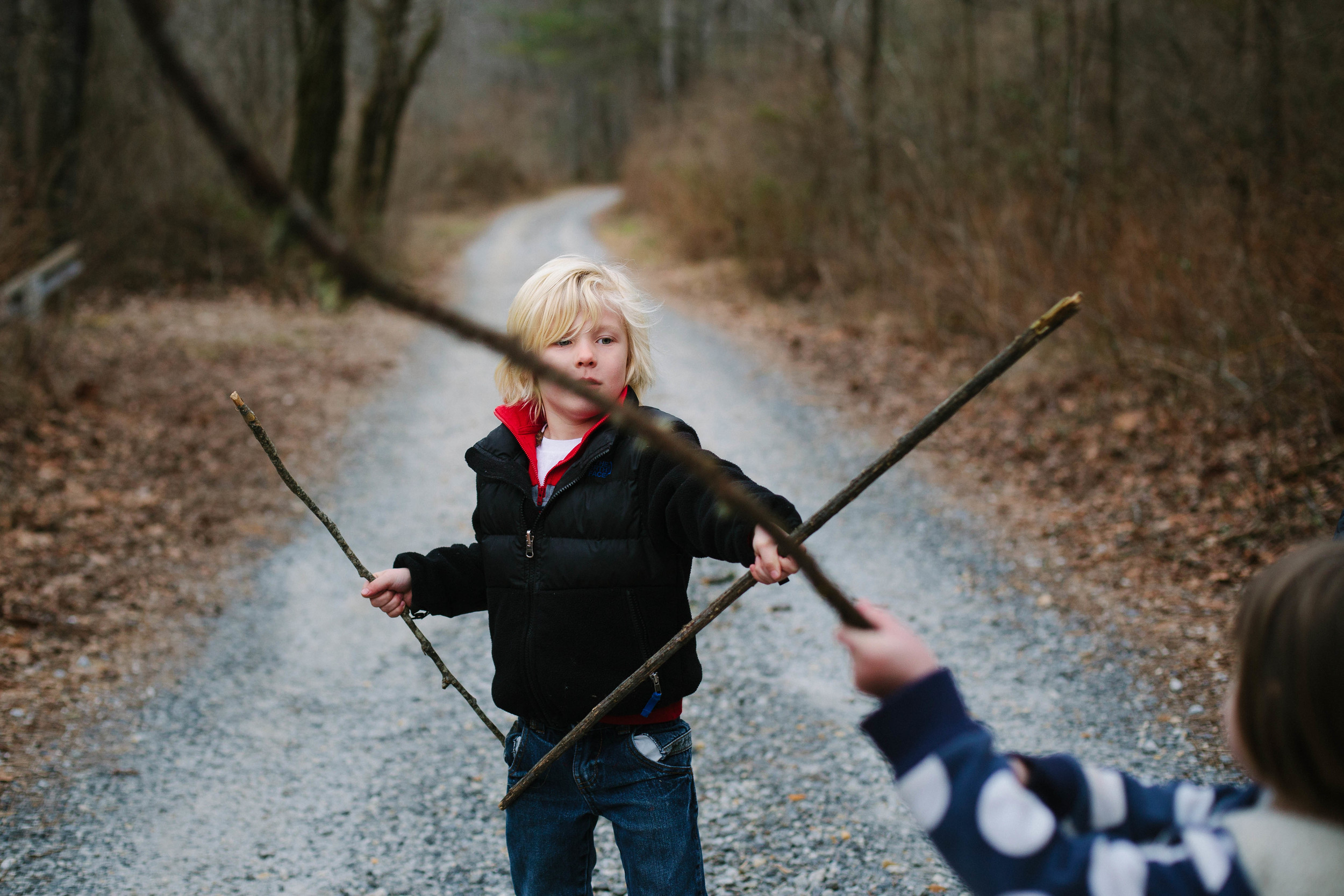 Image of boy and girl play sword fighting with sticks on gravel road in forest