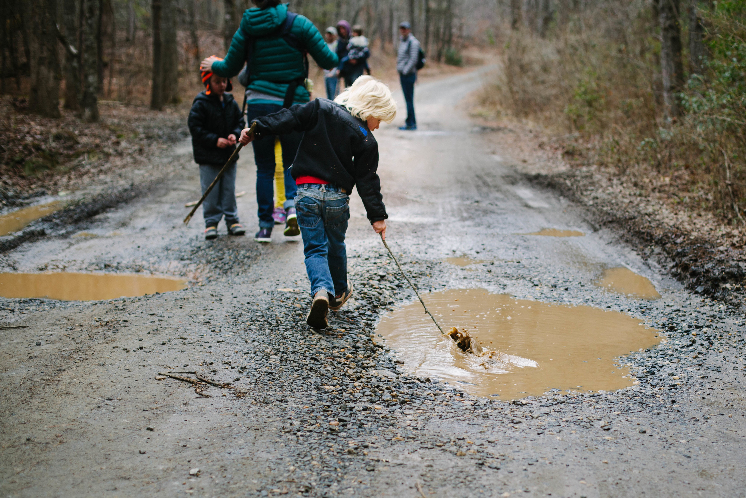 Image of boy running stick through a puddle on a gravel road in a forest