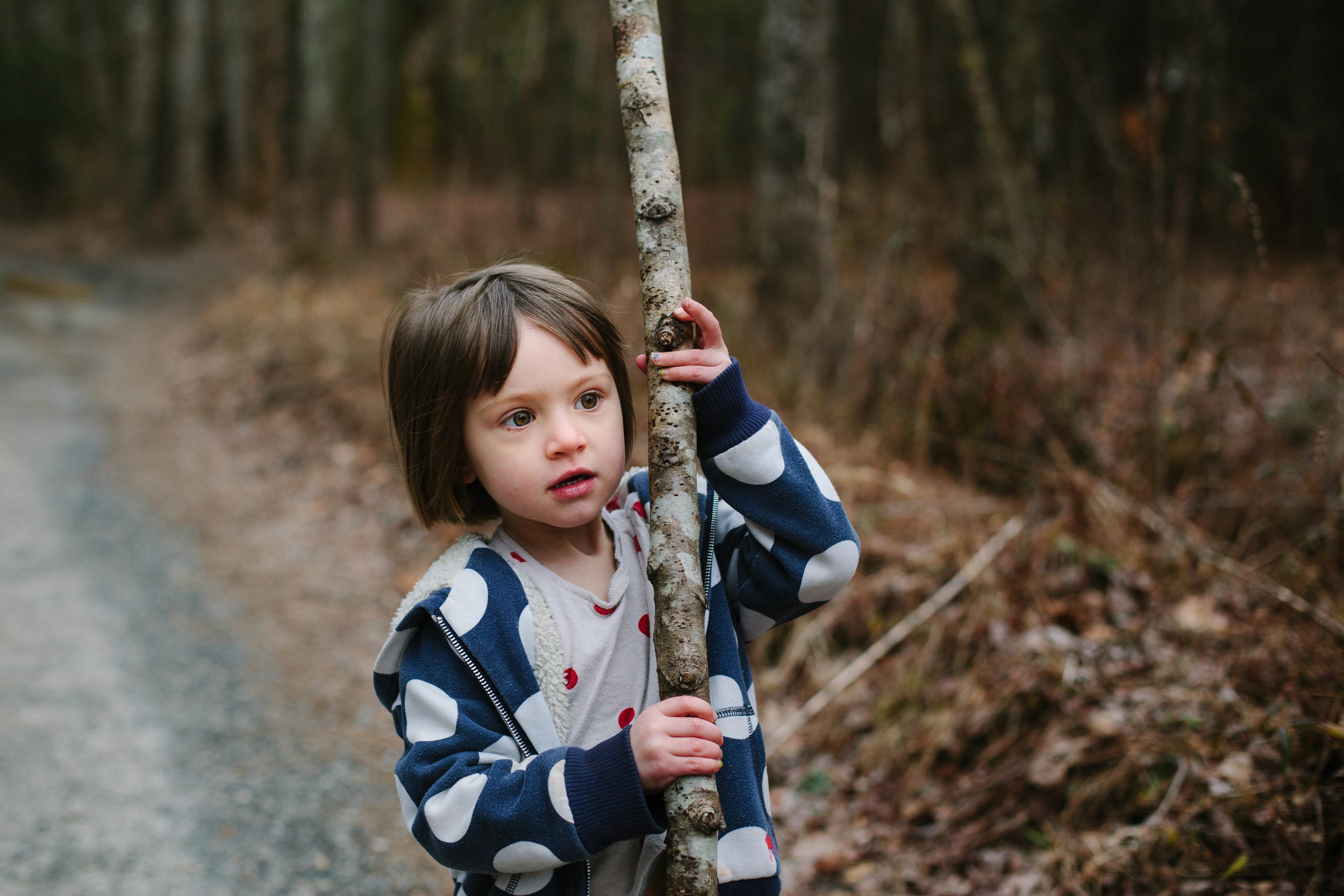 Image of girl with large stick on gravel road in the forest