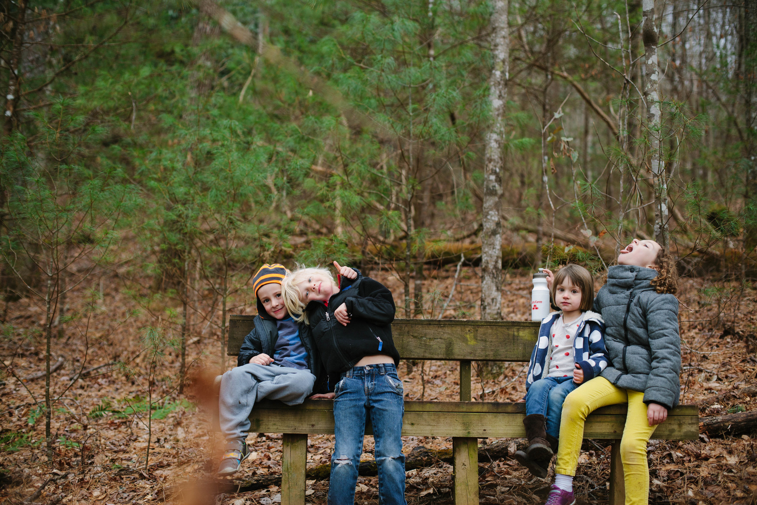 Image of children resting on a bench in a forest