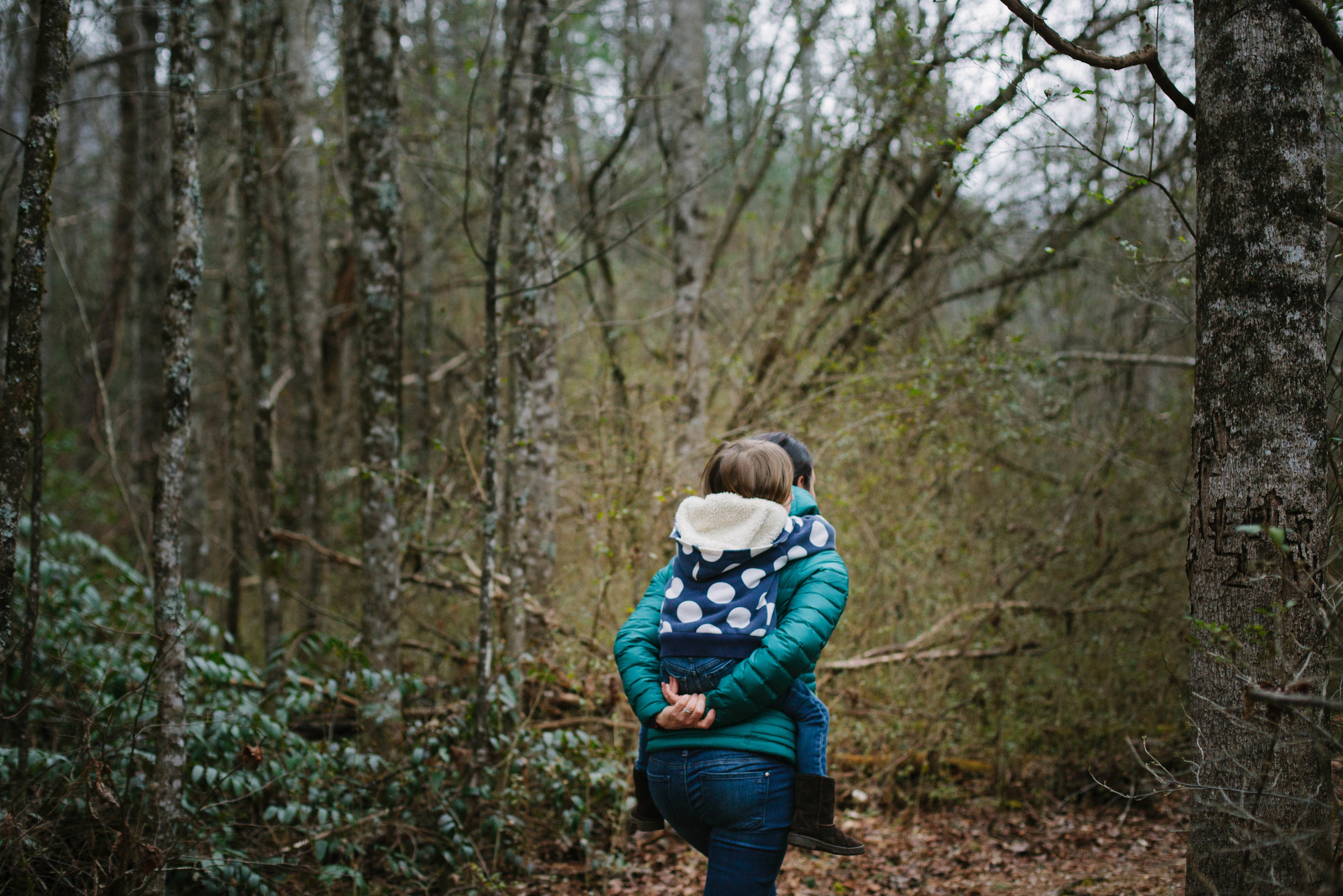 Image of woman carrying child on her back through a forest