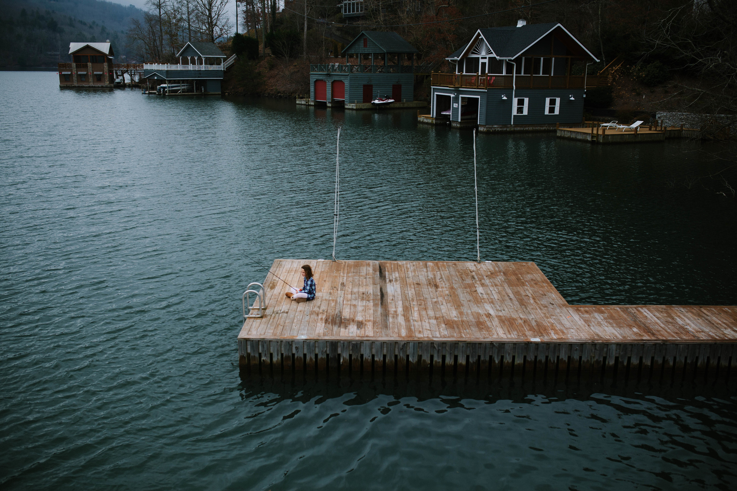 Image from above of girl sitting on dock fishing