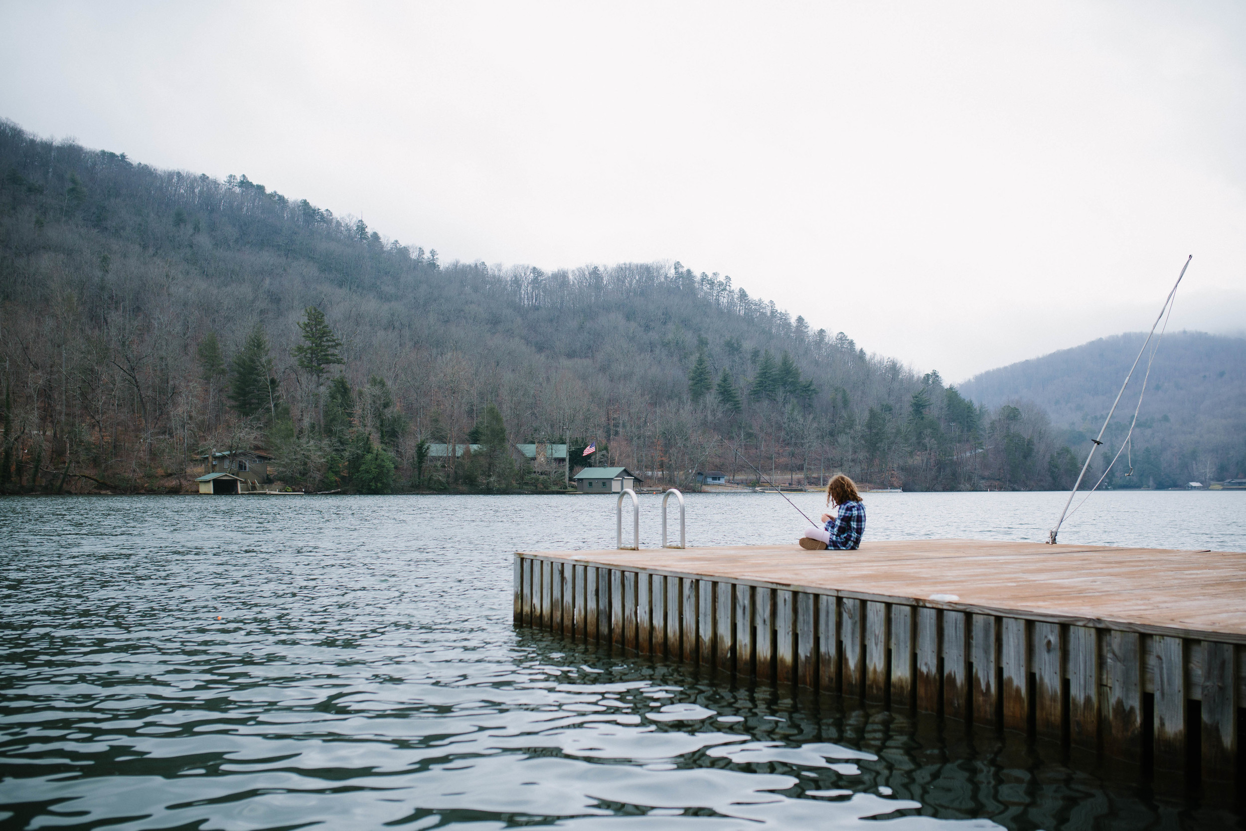 Image from behind of girl sitting on dock fishing