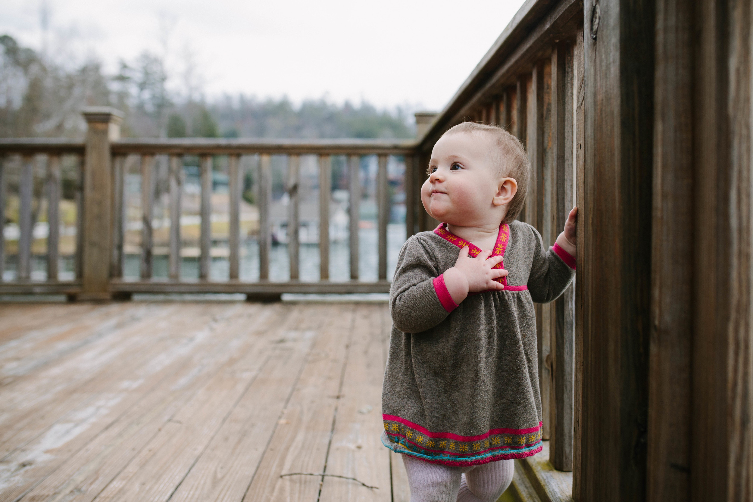 Image of baby looking back on deck with hand over heart
