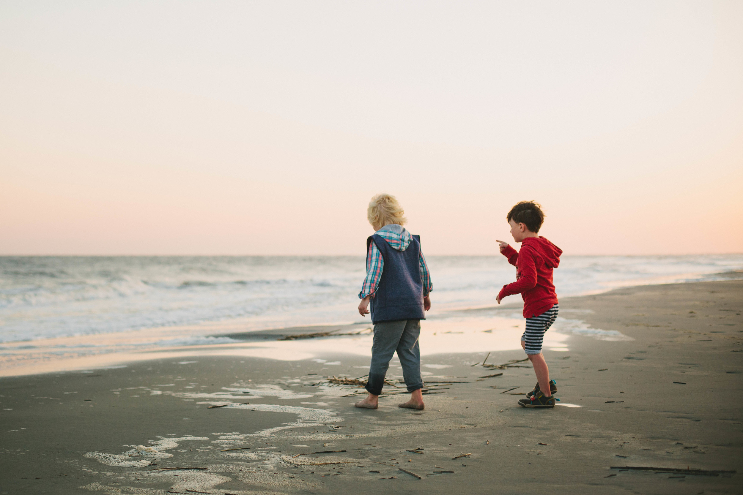 Image of two boys on the beach during sunset