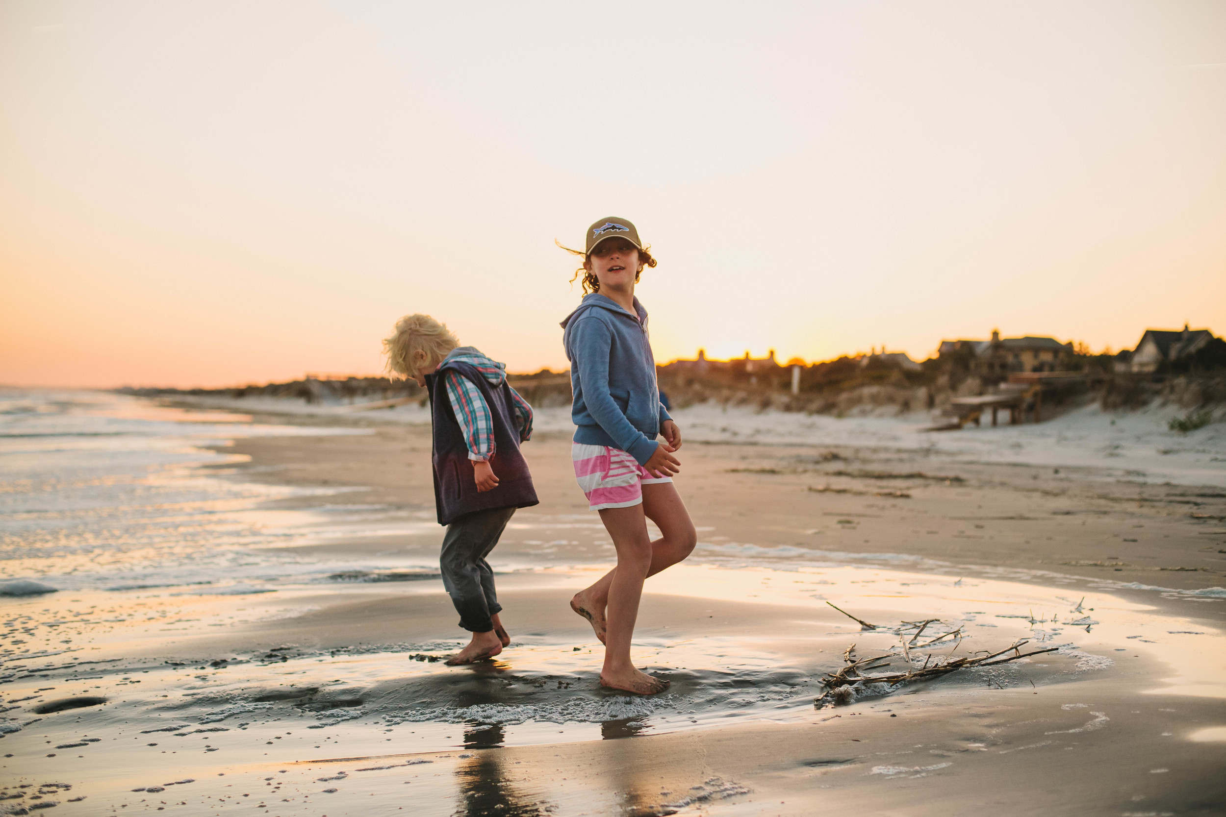 Image of girl and boy playing near the water at the beach