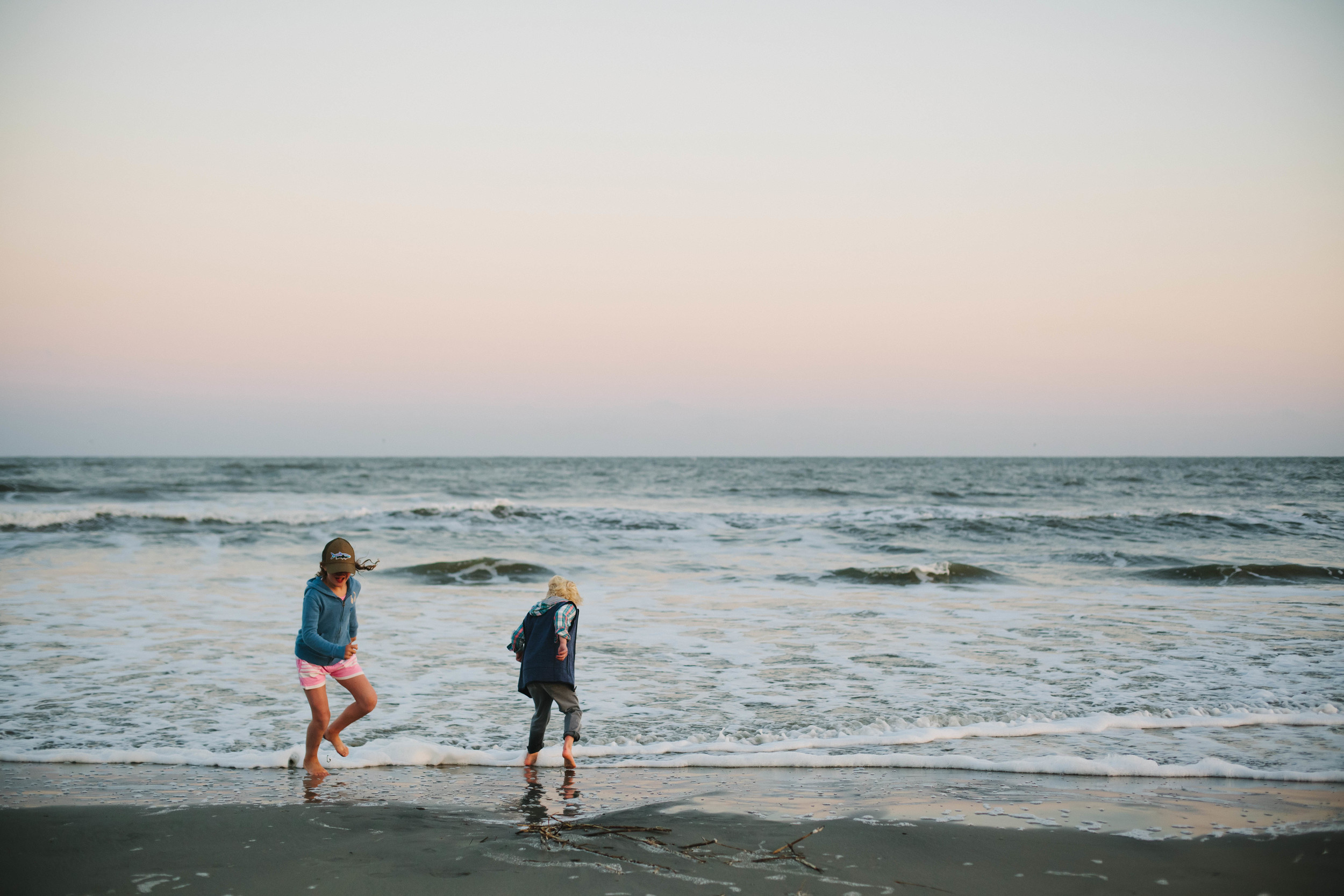 Image of boy and girl playing in the waves at the beach