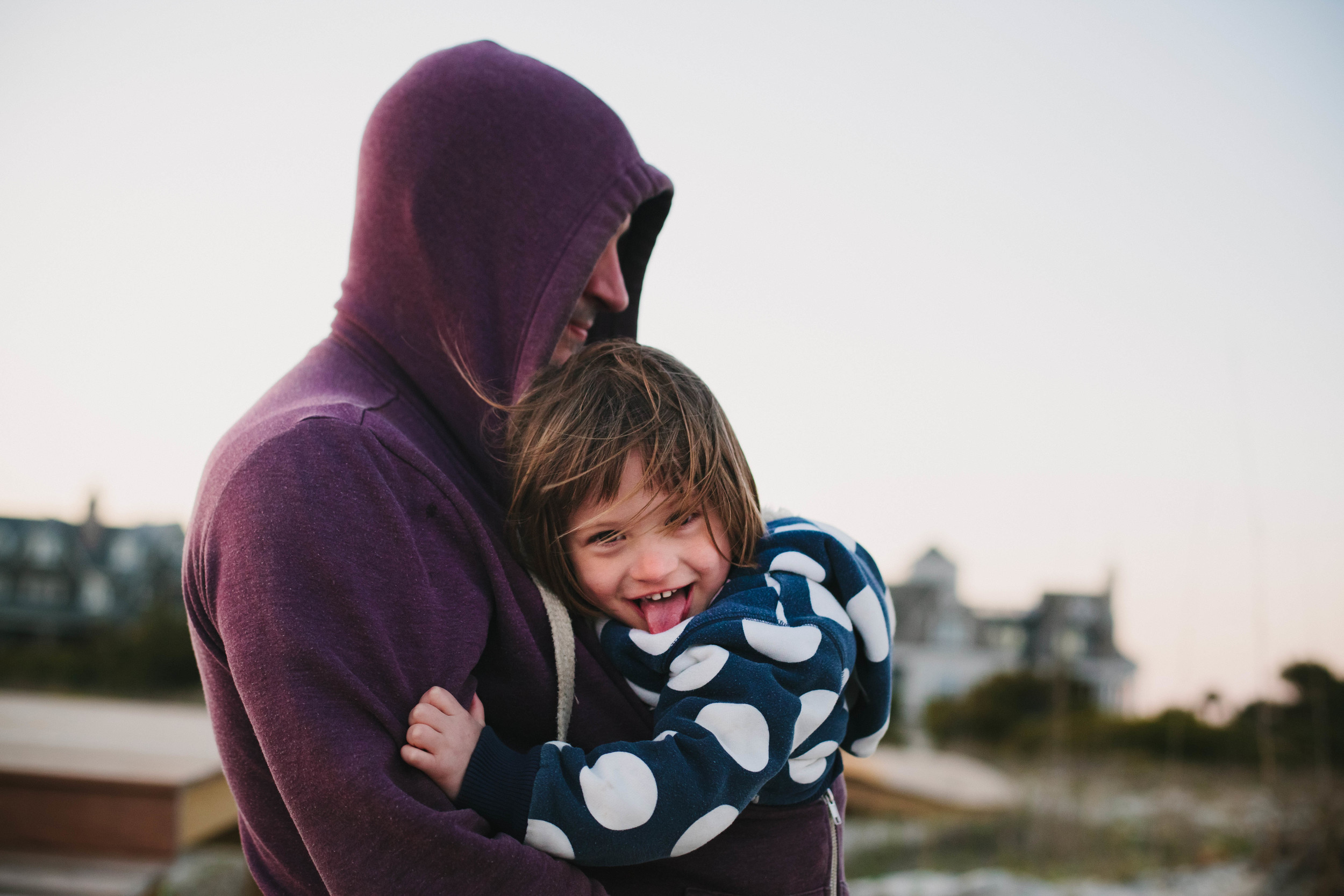 Image of girl keeping warm in her father's coat looking at the camera sticking out her tongue