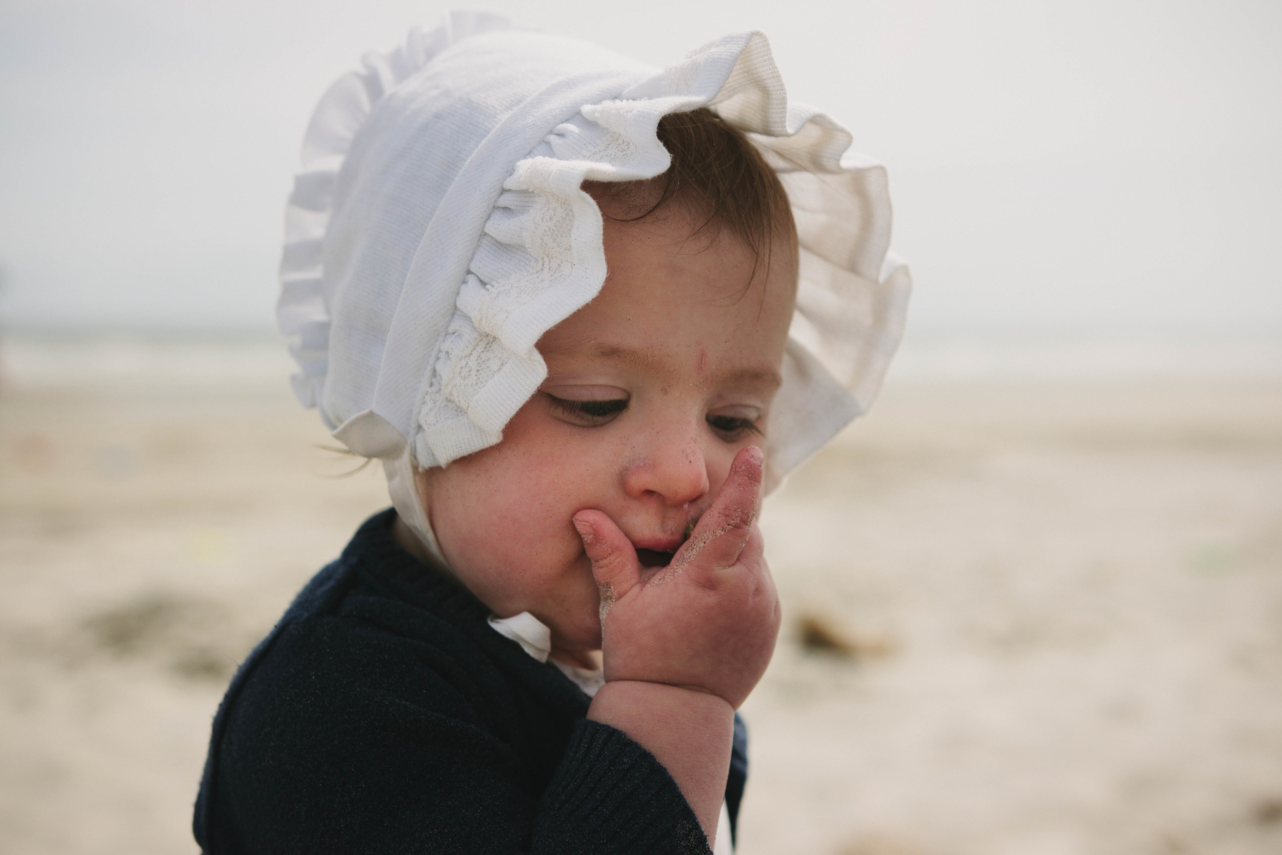 Image of baby in bonnet eating sand at the beach
