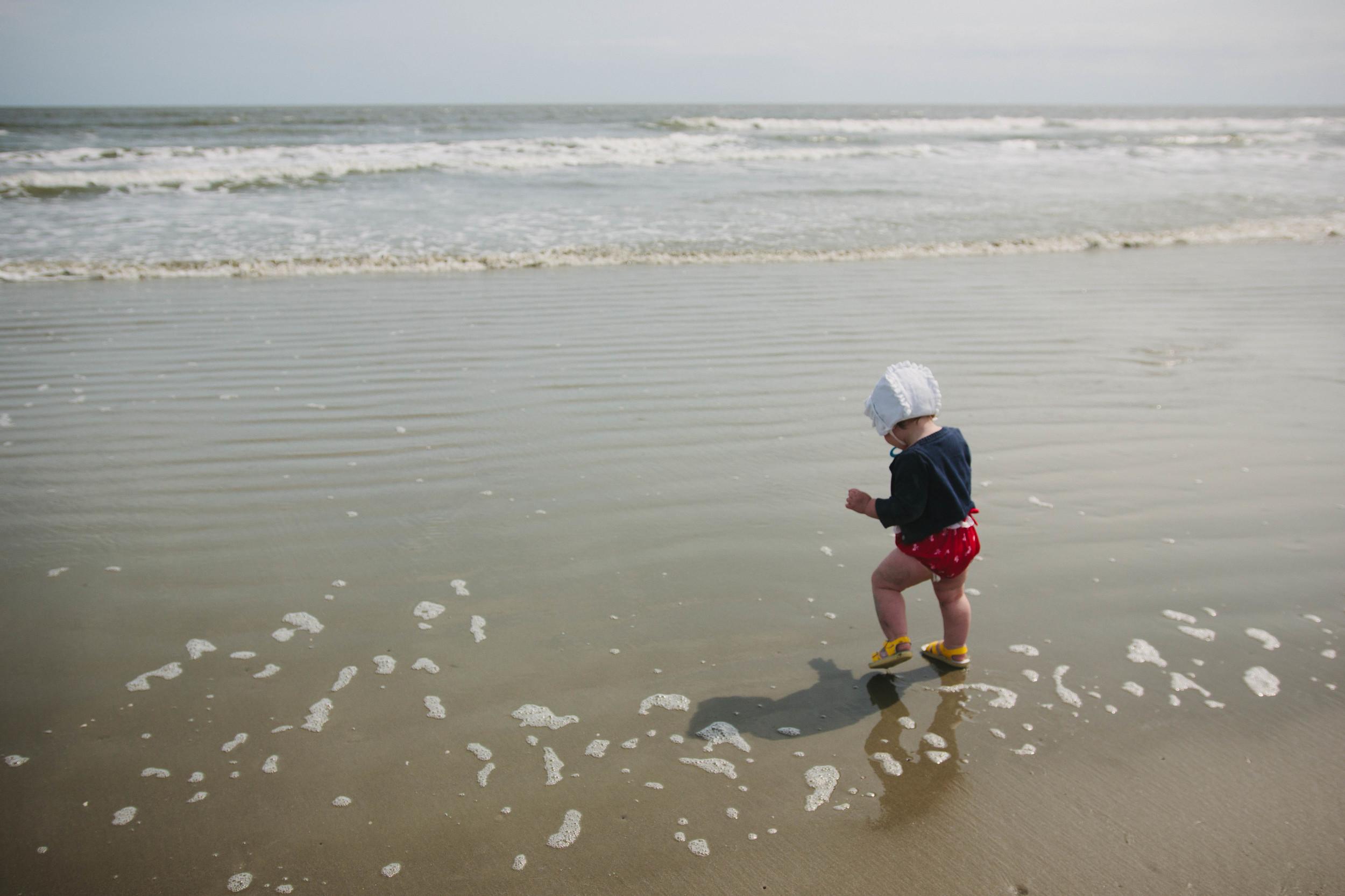 Image of baby walking along shore at a beach