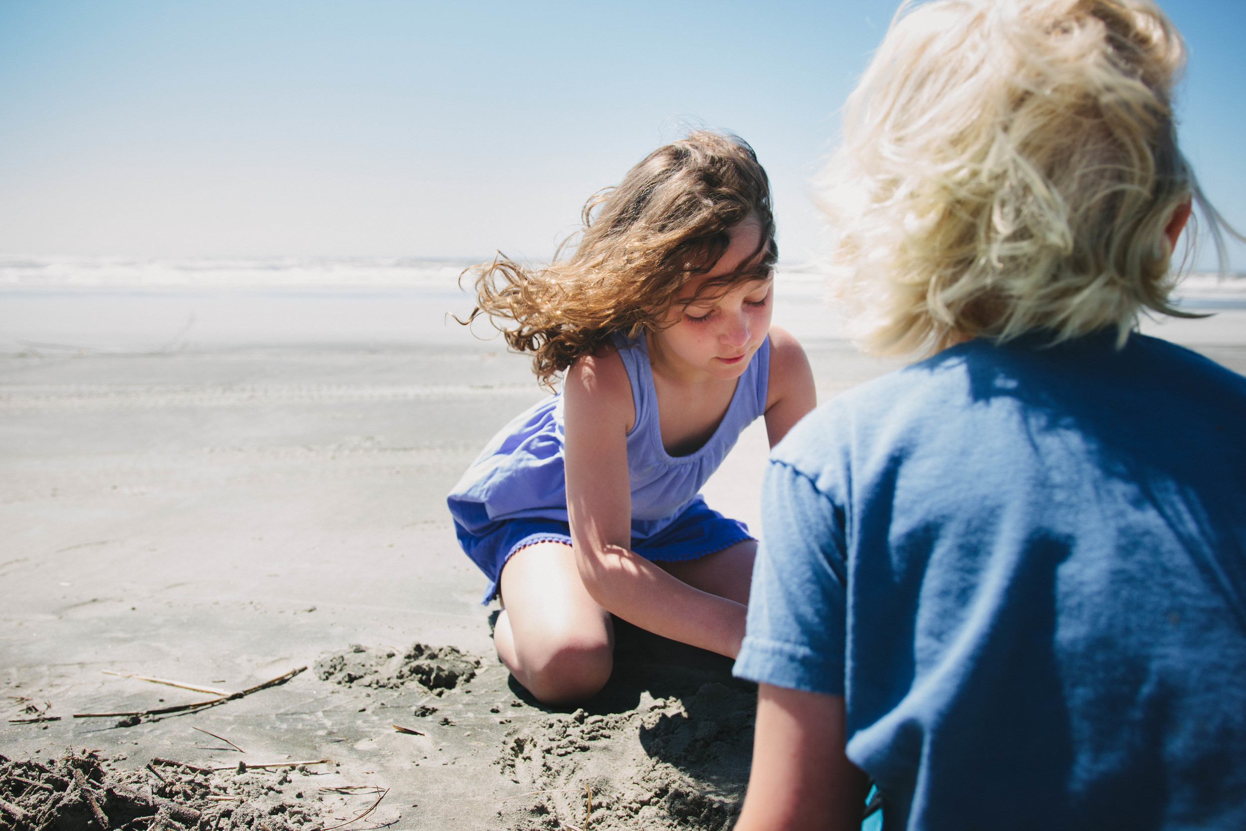 Image of girl a boy playing in the sand