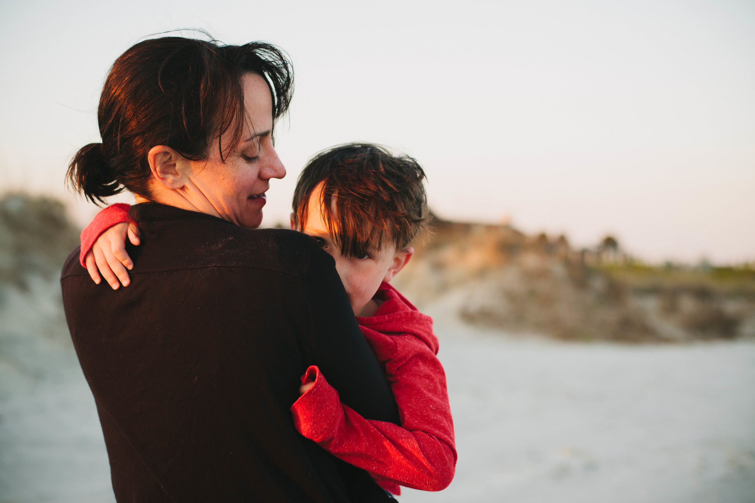 Image of mother holding and looking at her son at the beach