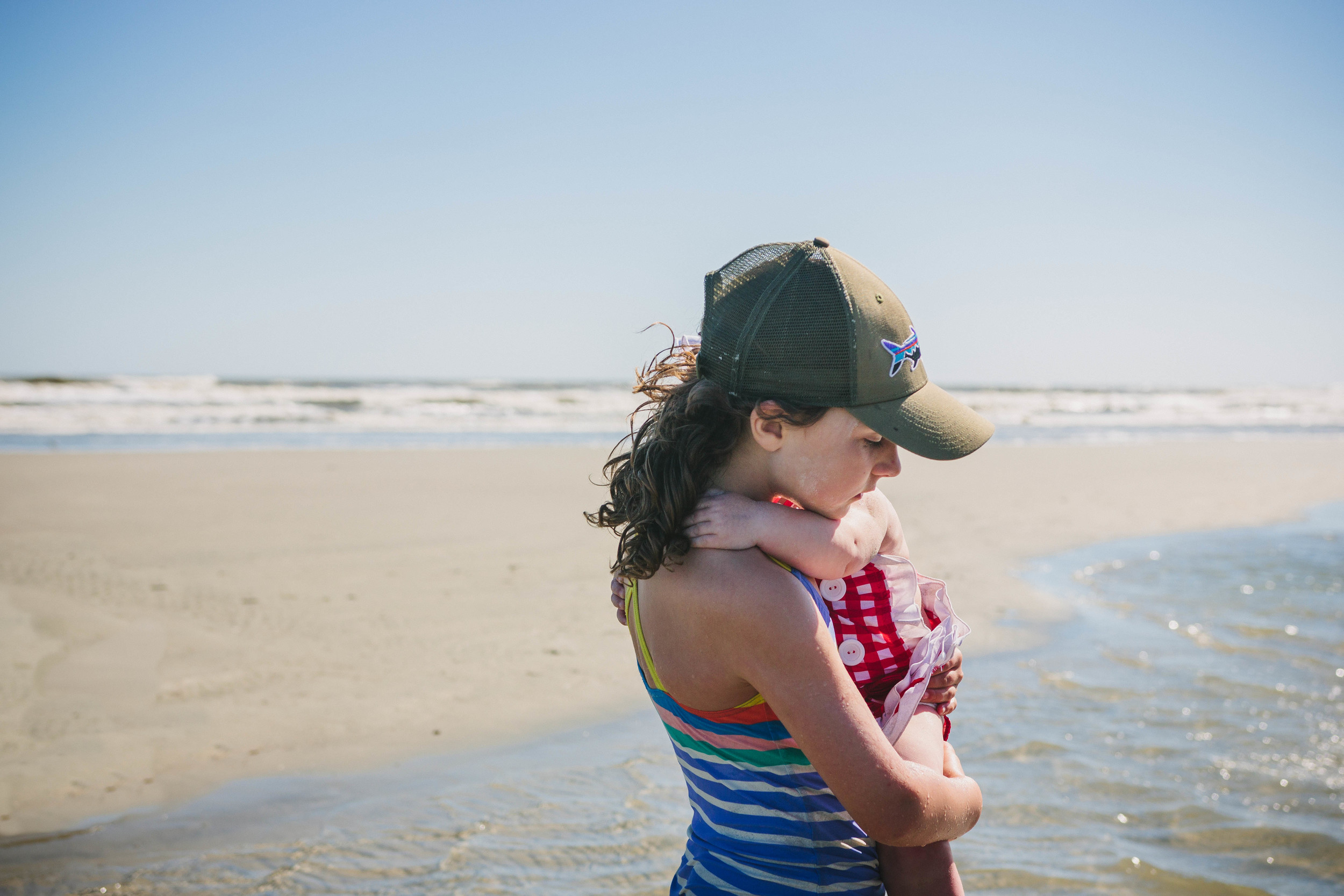Image of an older girl holding a baby at the beach