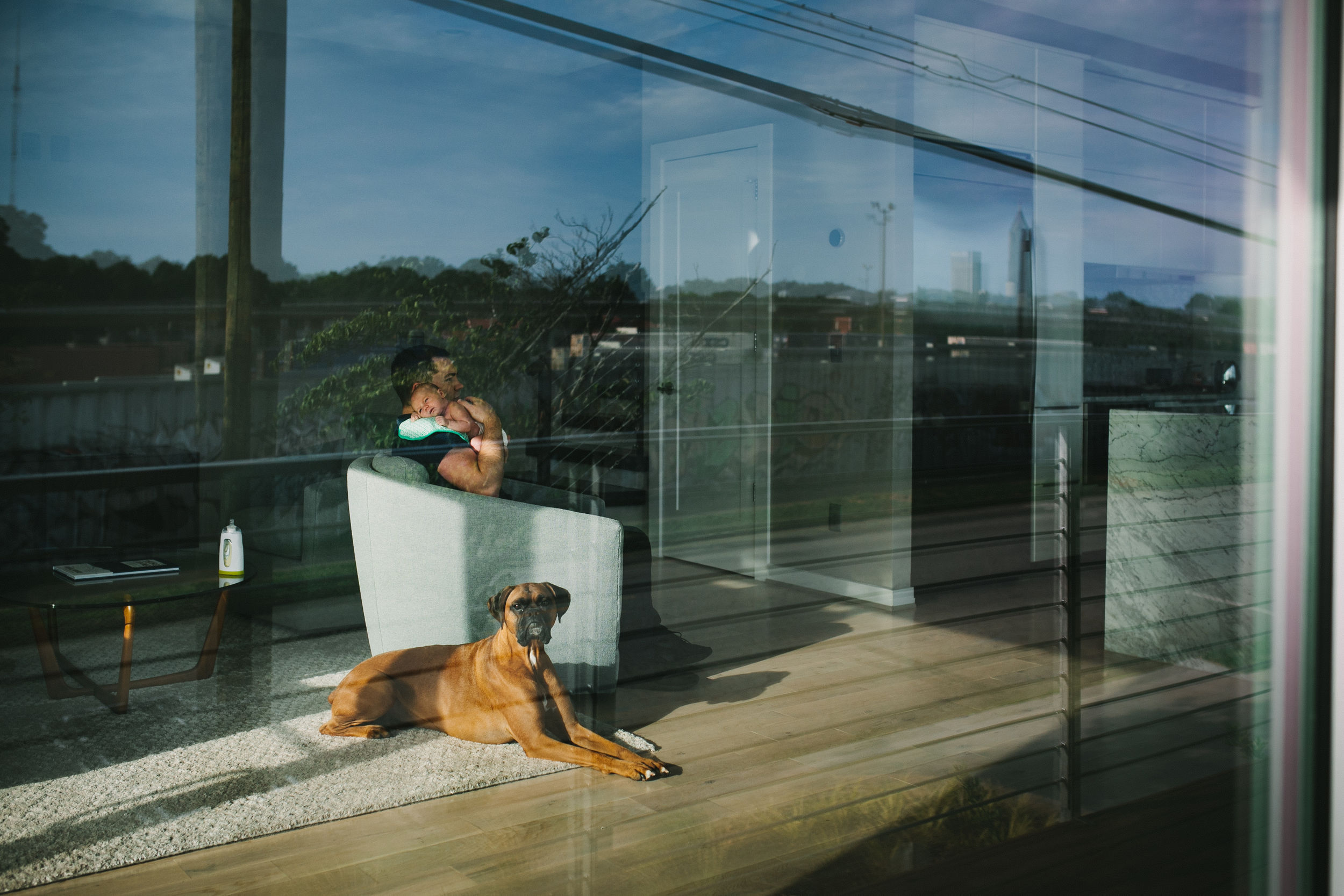 image through window of father holding baby with dog nearby and reflection from at home newborn documentary photography session
