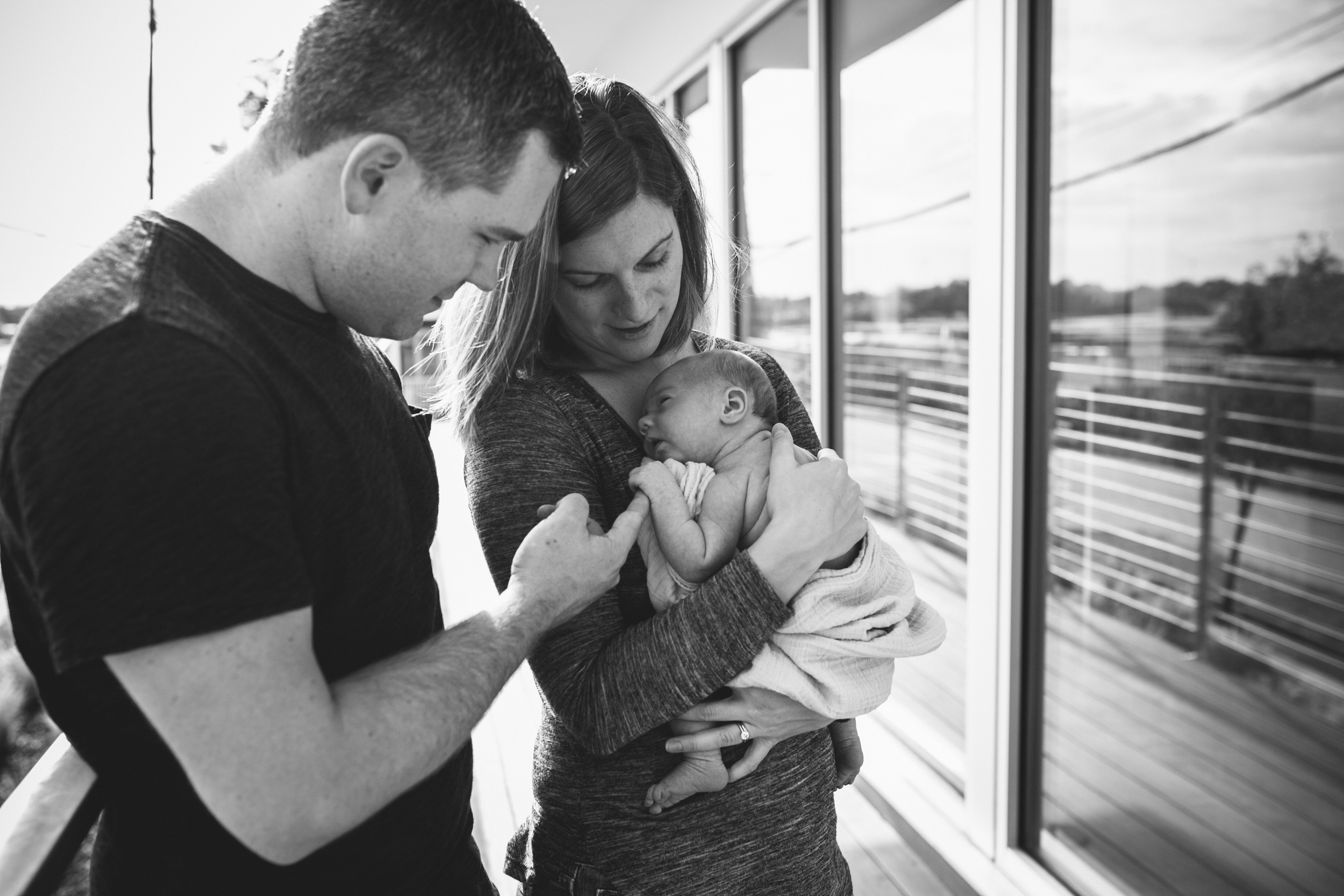 image of newborn holding father's finger while in mother's arms from at home atlanta newborn documentary photography