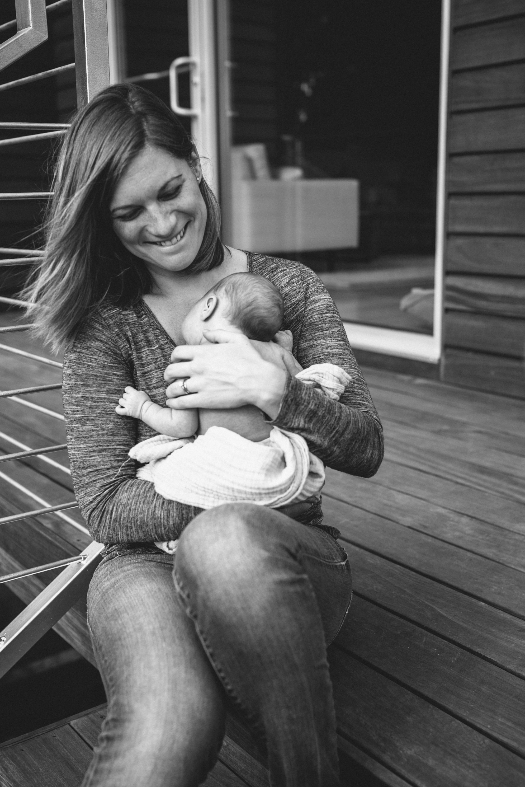 image of mother holding newborn and smiling on steps from at home atlanta newborn documentary photography session