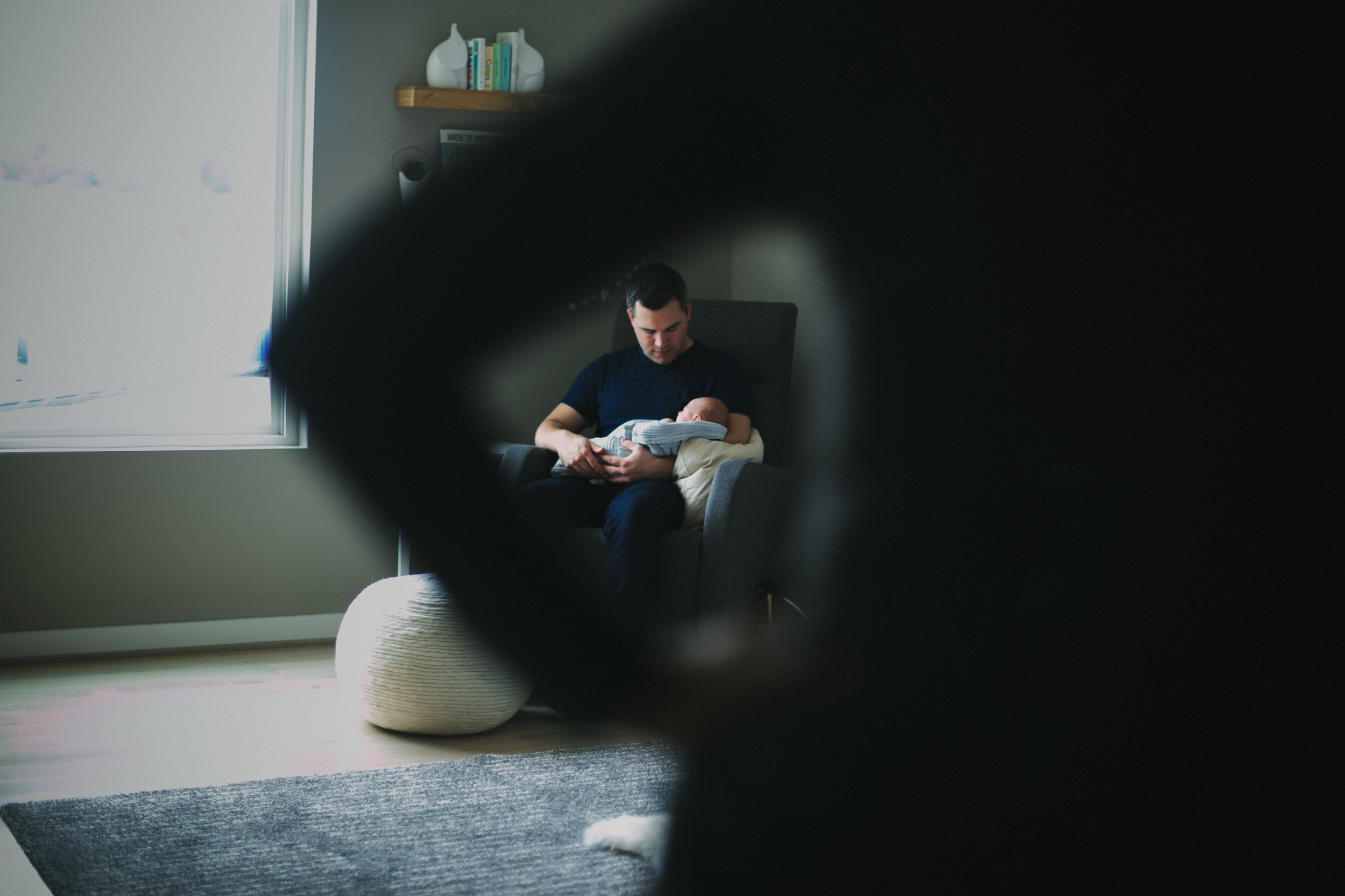 image of father rocking and looking at newborn through mother's arms from at home atlanta newborn documentary photography session