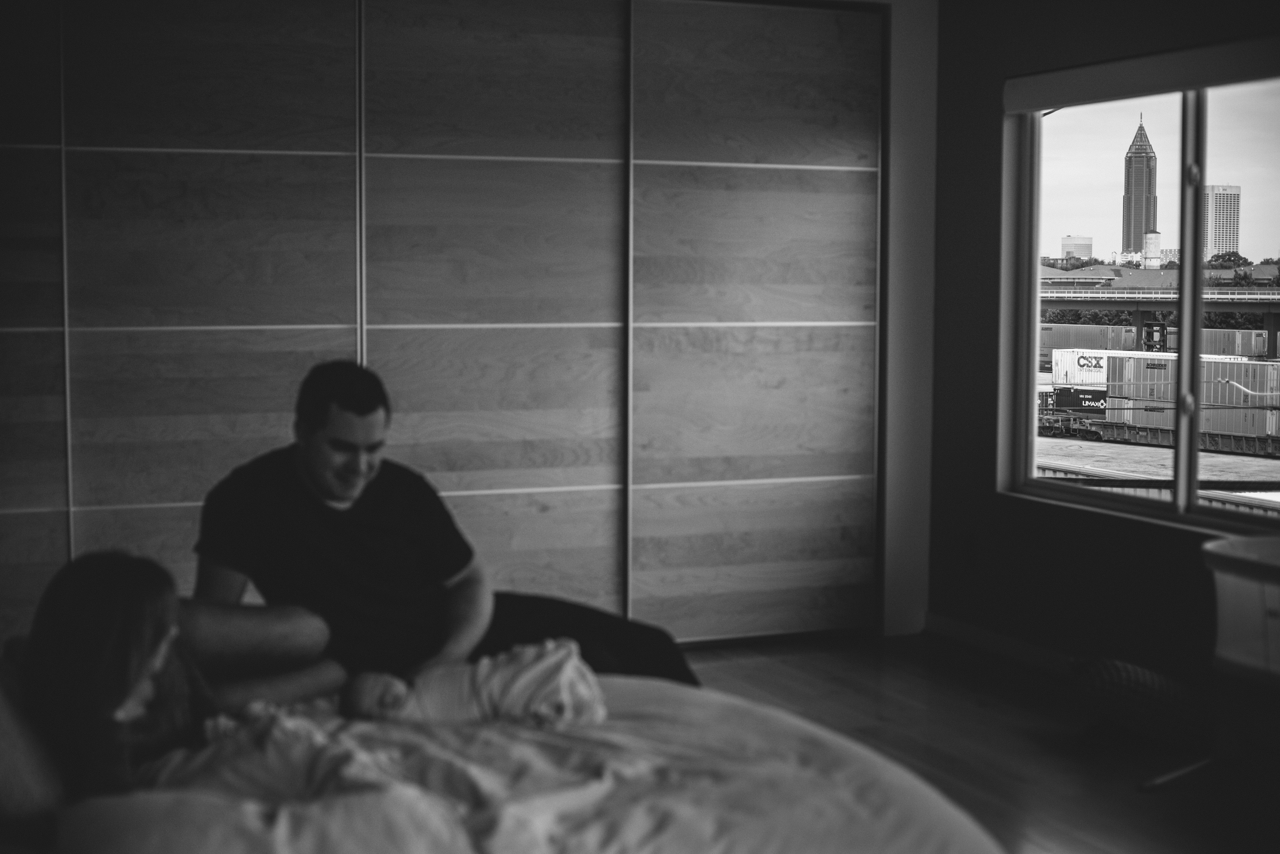 image of family on bed with city through window in focus in background from at home atlanta newborn documentary photography session