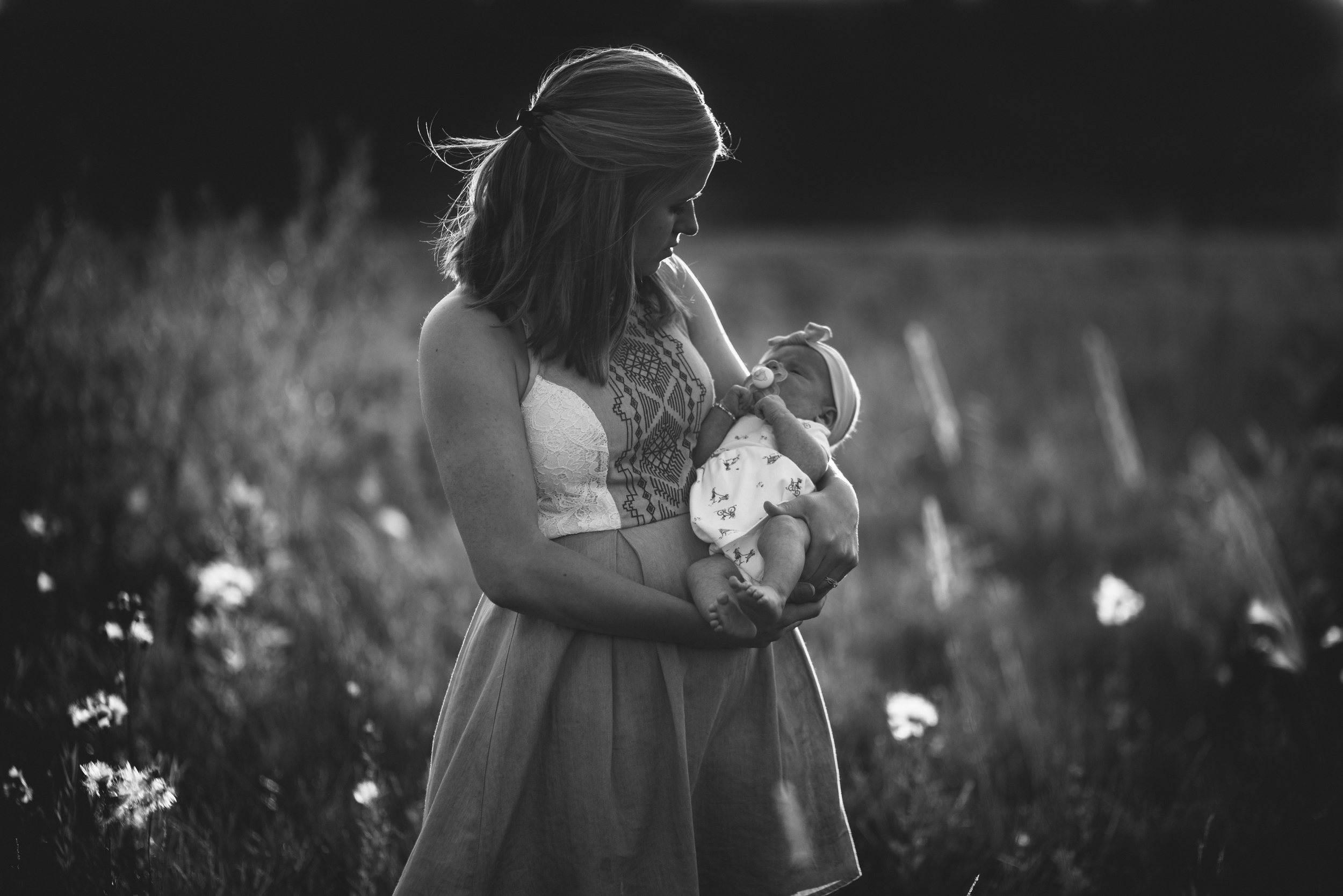 image of mother holding and looking down at her newborn baby