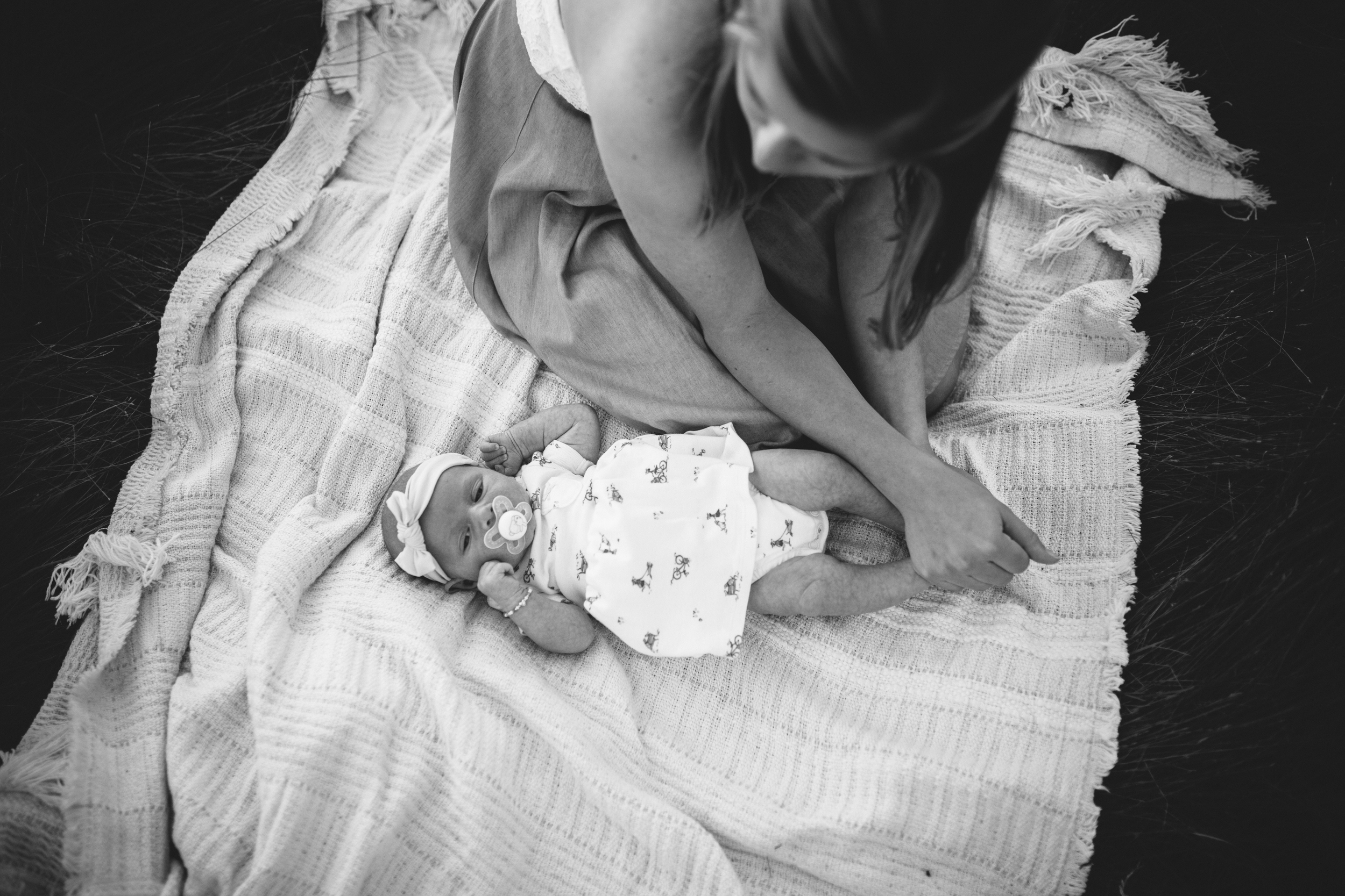image from above of mother warming up newborn's feet