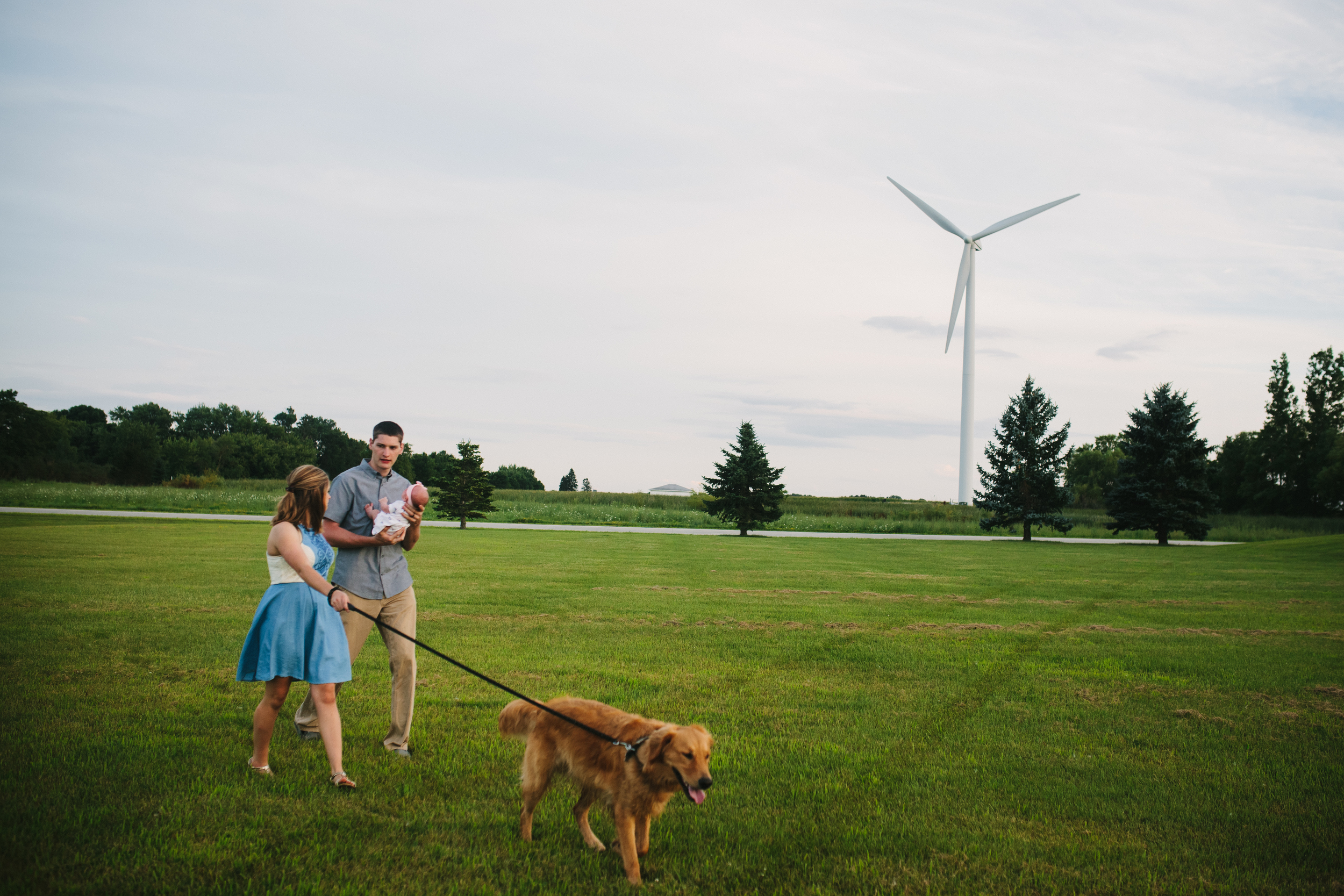 image of mother and father with newborn baby and dog with windmill in the background