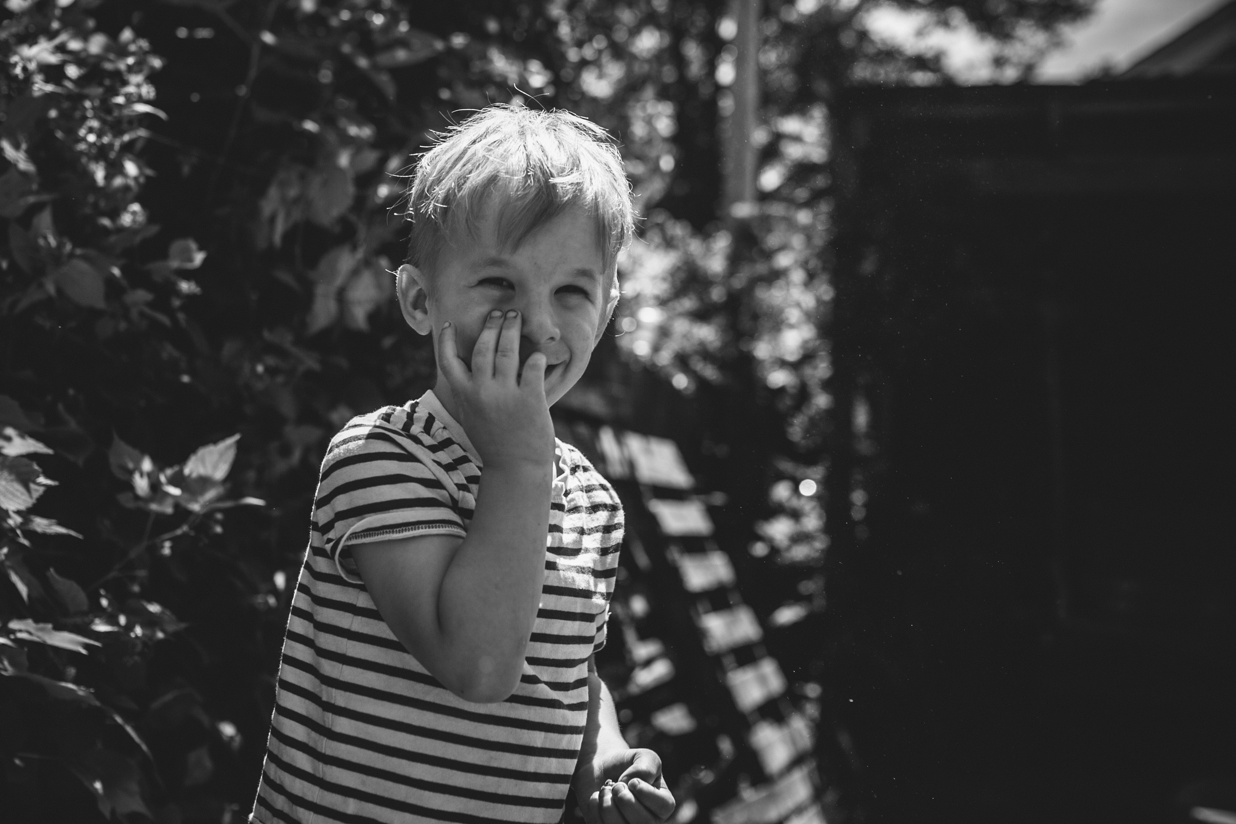 image from family documentary session of boy smiling and partially covering his face with his hand