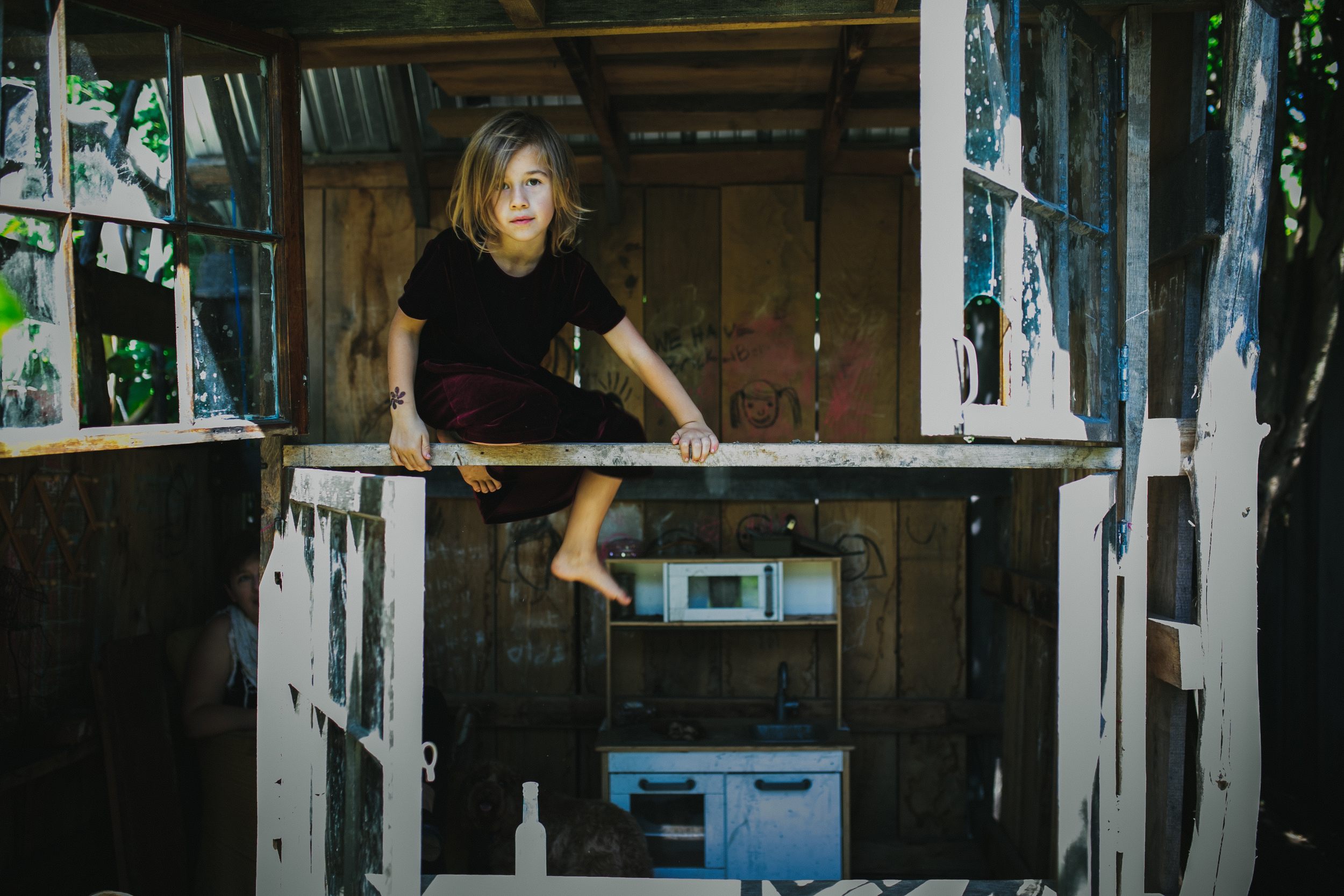 image from family documentary session of a girl climbing on playhouse