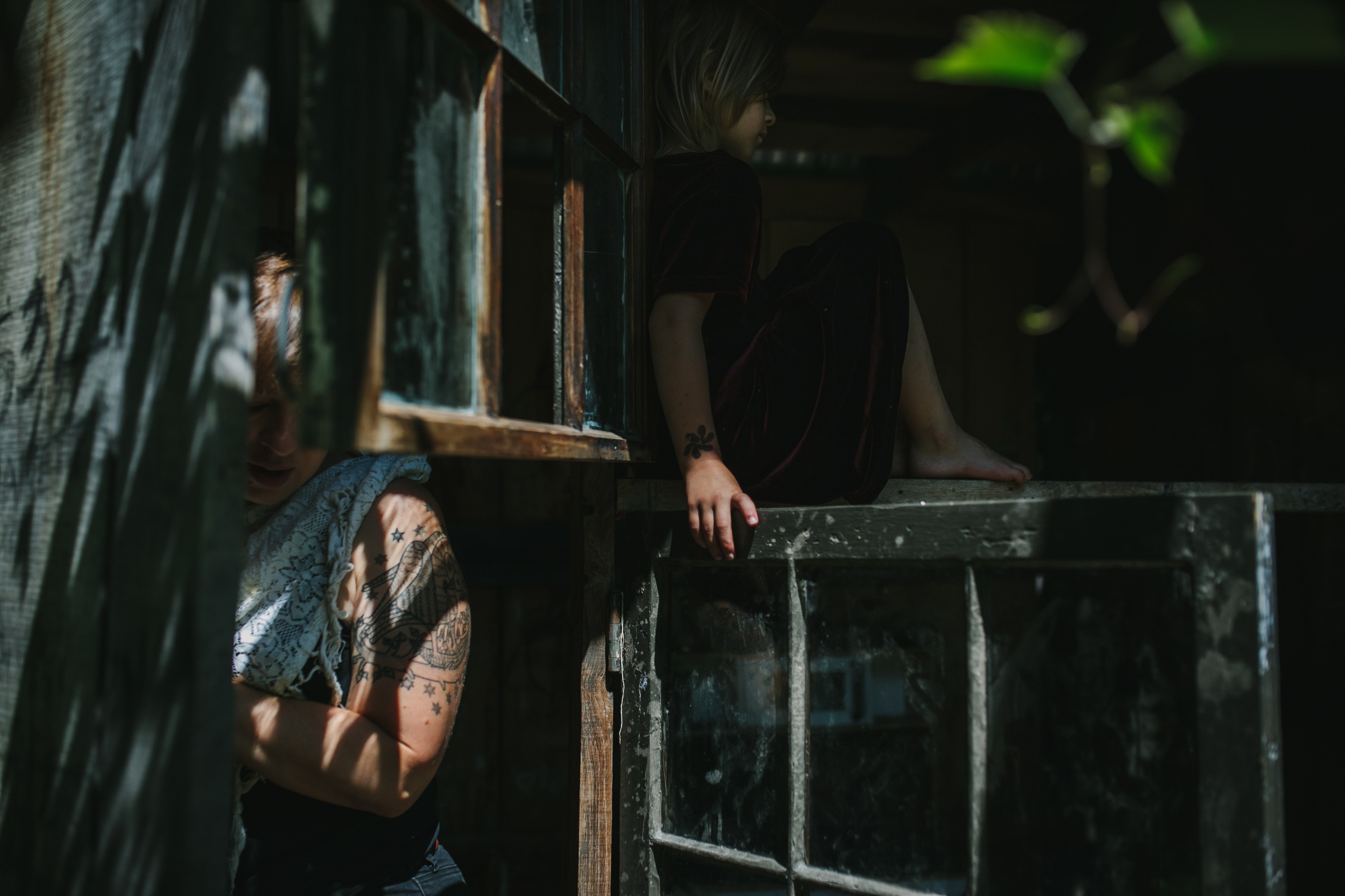 image from family documentary session of girl climbing in playhouse with drawn tattoo on hand and mother in background with tattoo showing