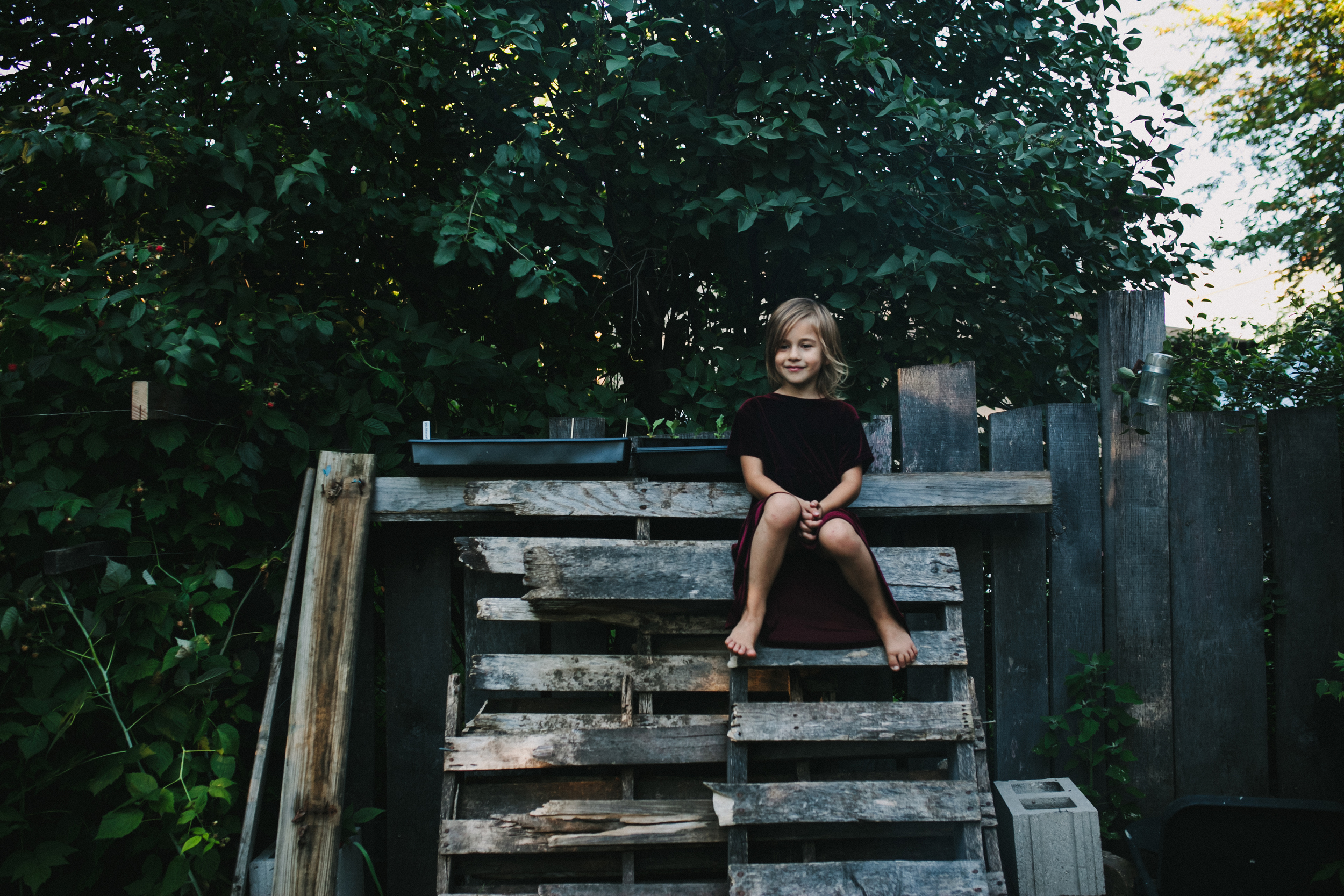 image from family documentary session of a girl sitting on the top of wooden pallets
