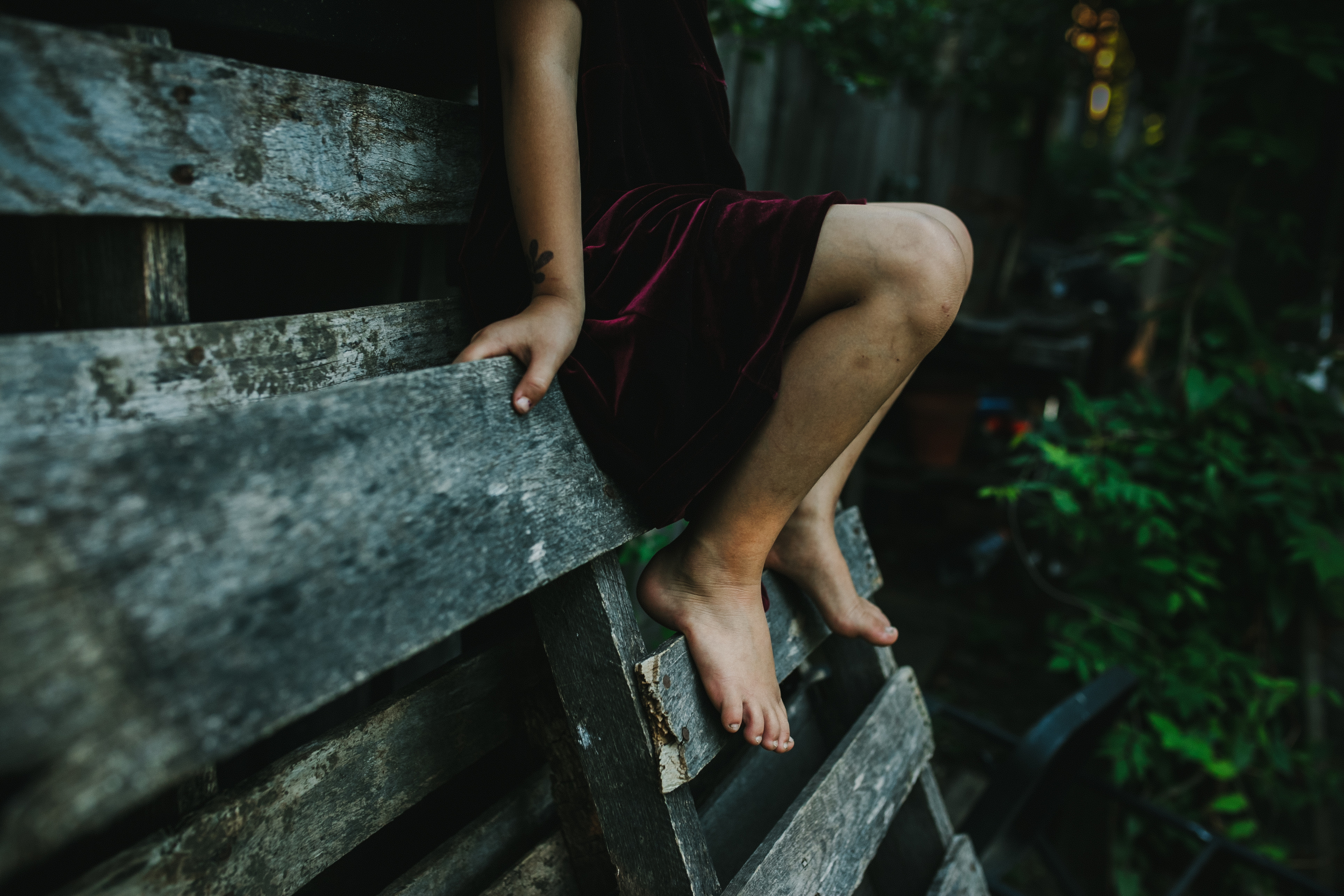 image from family documentary session of a girl's bare feet sitting on a wooden pallet