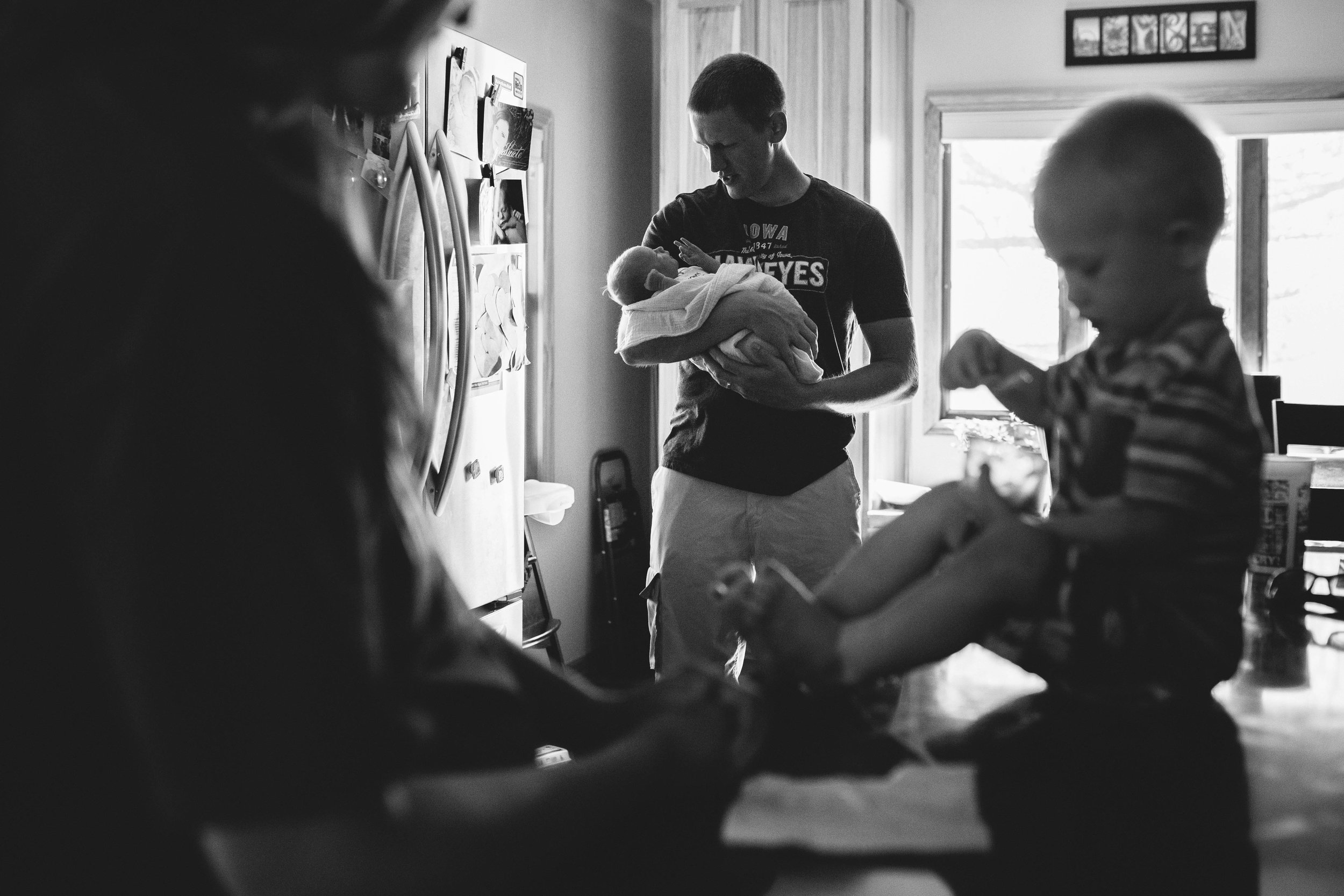 man holding newborn behind mother and son eating breakfast from newborn documentary family photography session