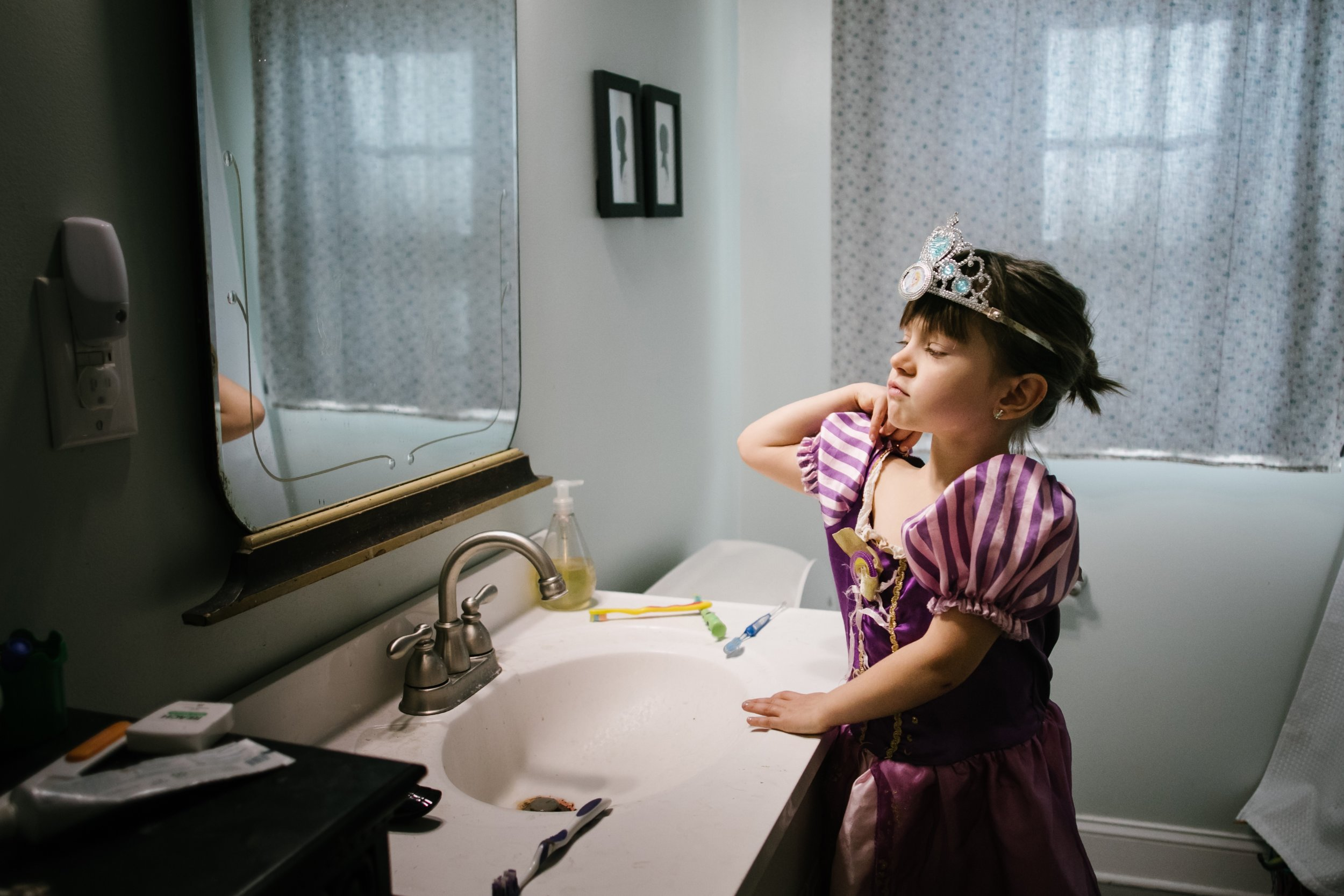 Girl standing in front of a mirror with a princess dress and hat on while flexing her muscles