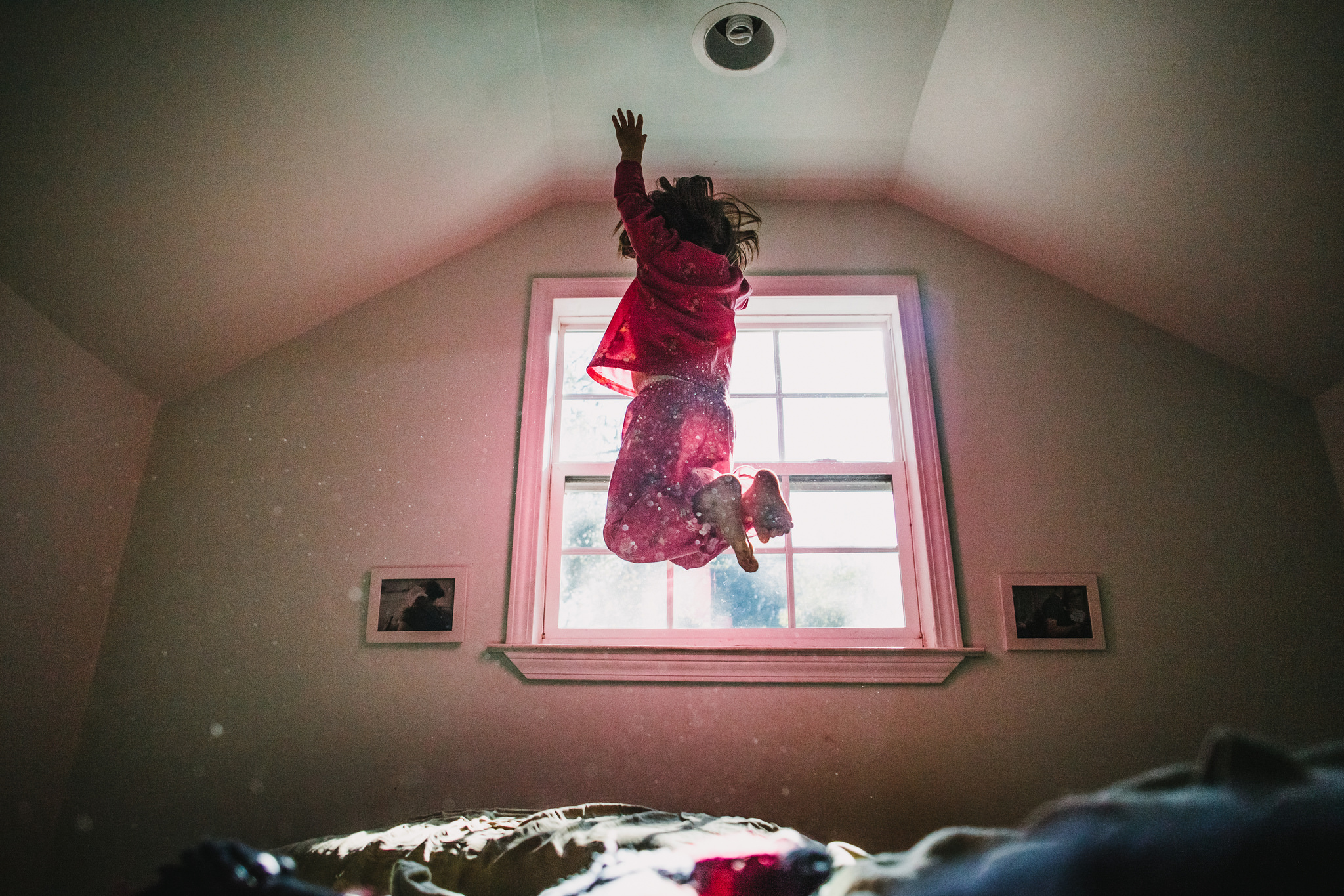 Girl in her pajamas jumping on a bed in the window light with dust floating