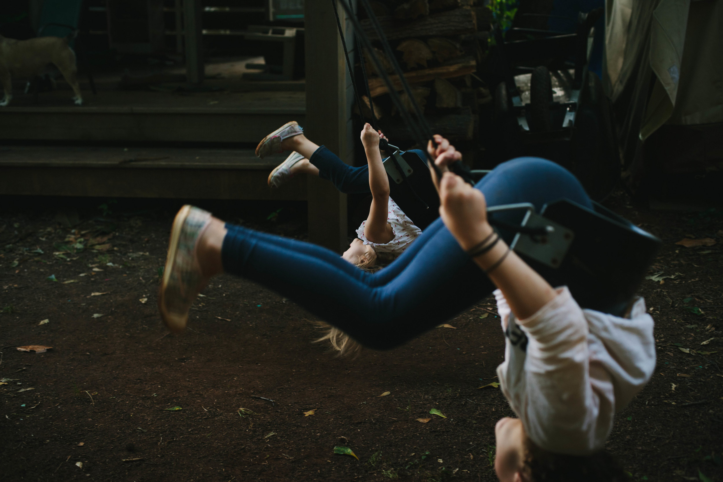 two girls doing a flip on a swing at the time