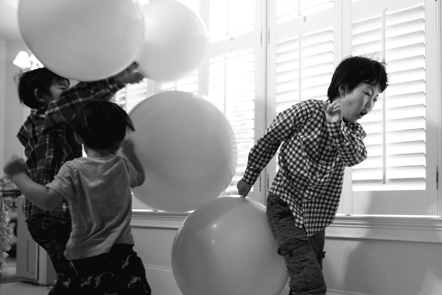 boy running from a balloon fight from family documentary photography session in atlanta