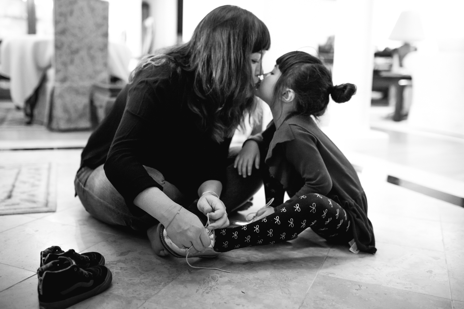 mother and daughter kissing during shoe tying from a family documentary photography session in atlanta