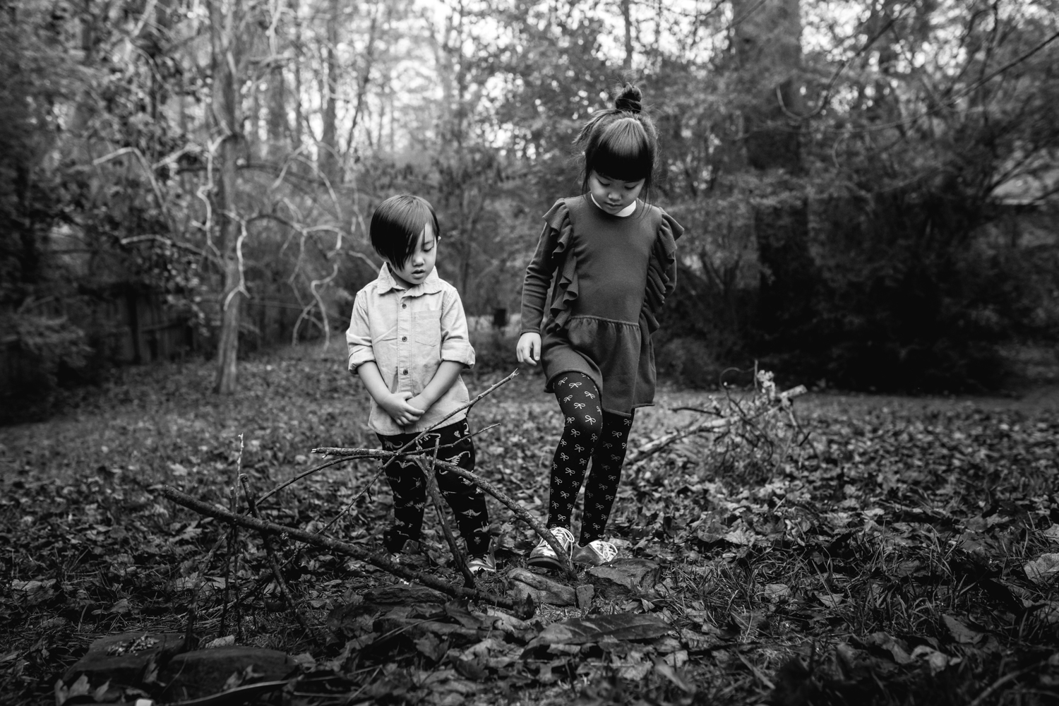 Brother and sister stand in a backyard with trees from family documentary photography session in atlanta
