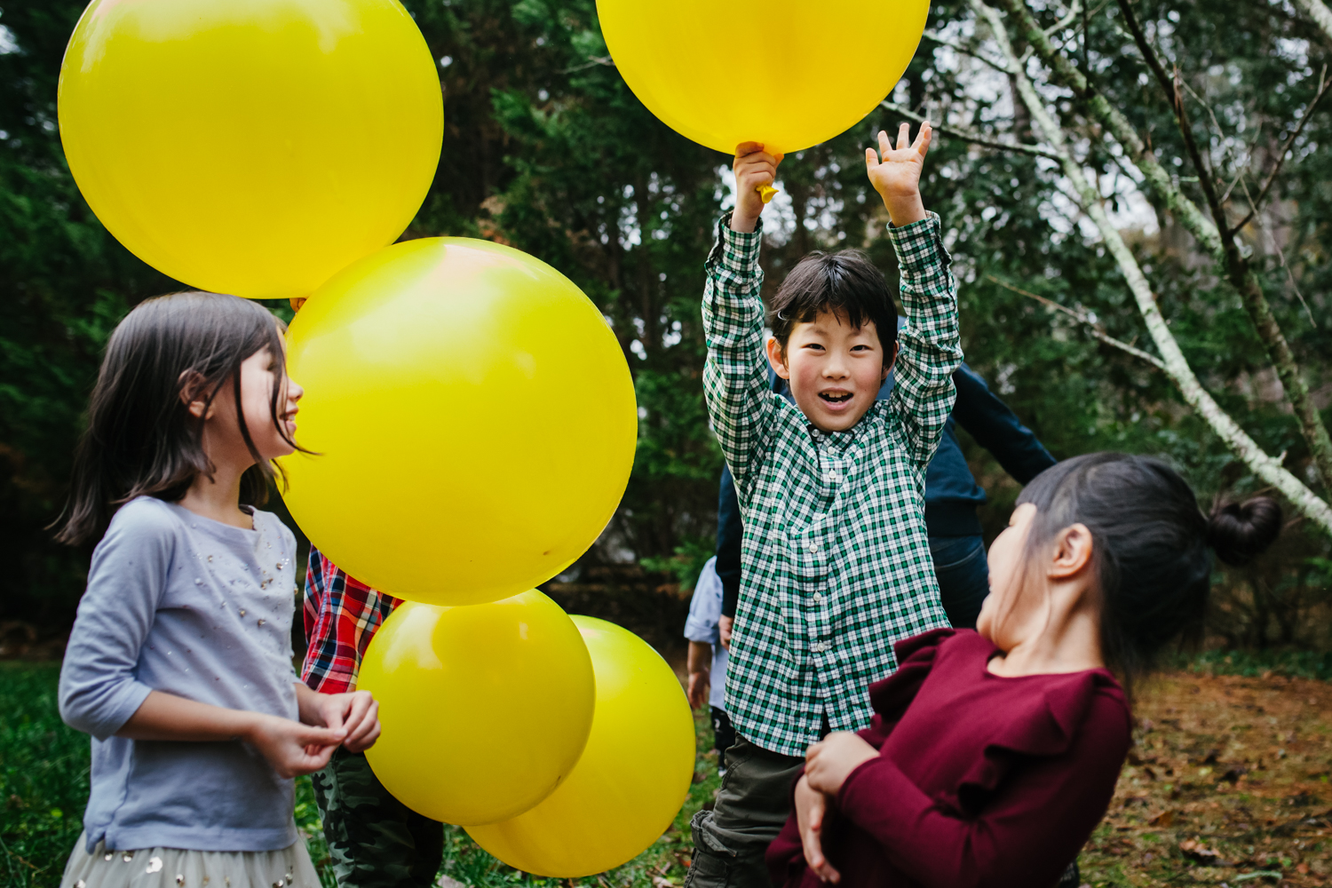 cousins play with big yellow balloons during a family documentary photography session in atlanta