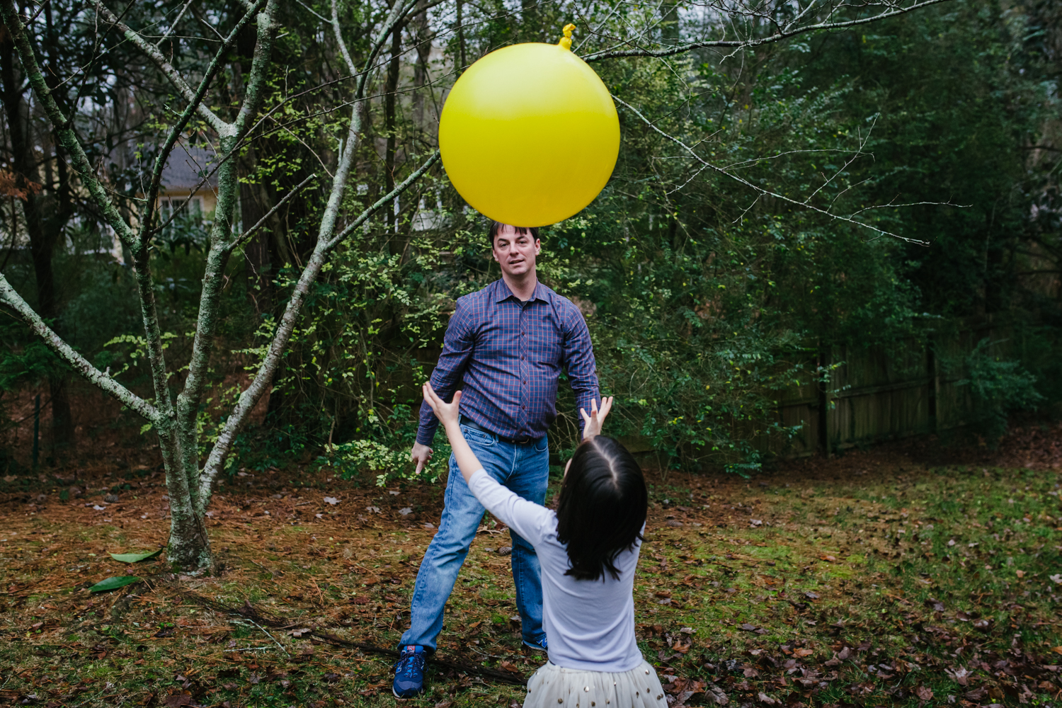 father and daughter play catch with a big yellow balloon during a family documentary photography session in atlanta
