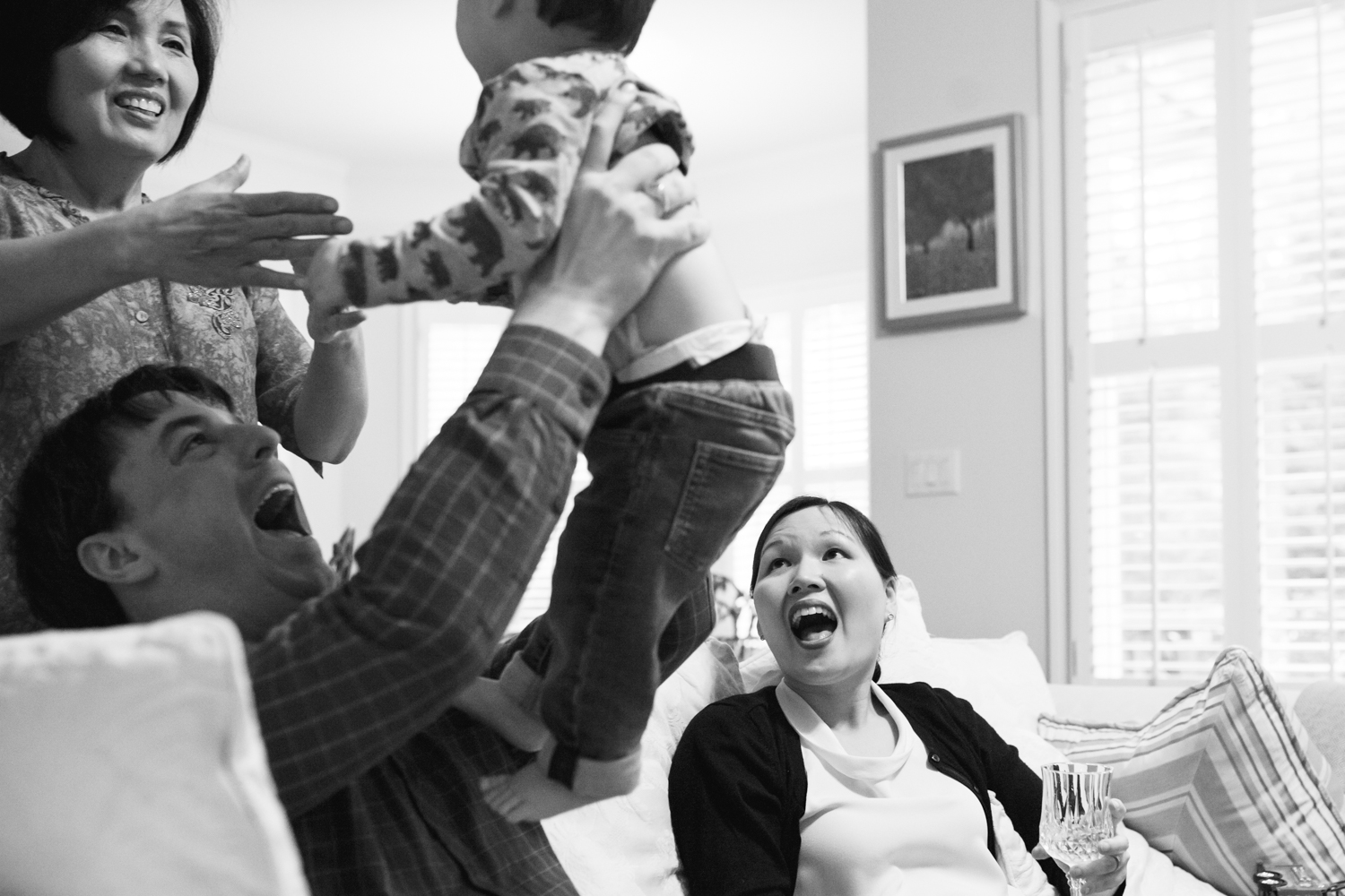 father holds son up to grandmother as mother looks on from family documentary photography session in atlanta
