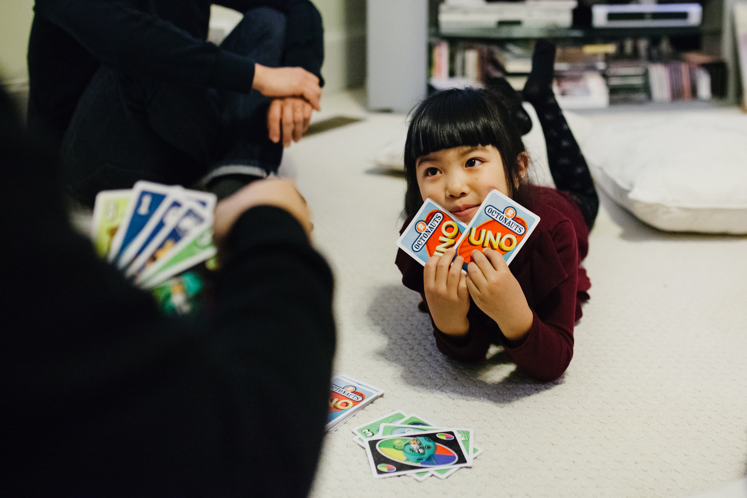 Girl plays uno with her uncle during a family documentary photography session in atlanta