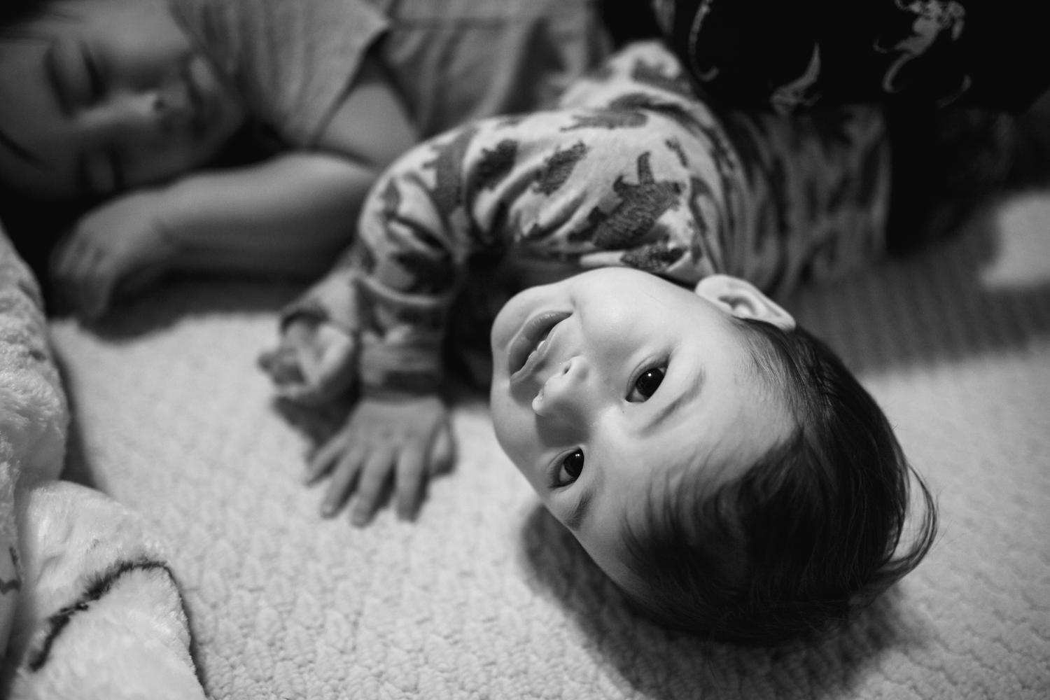 boy looks up at the camera from on the floor during a family documentary photography session in atlanta