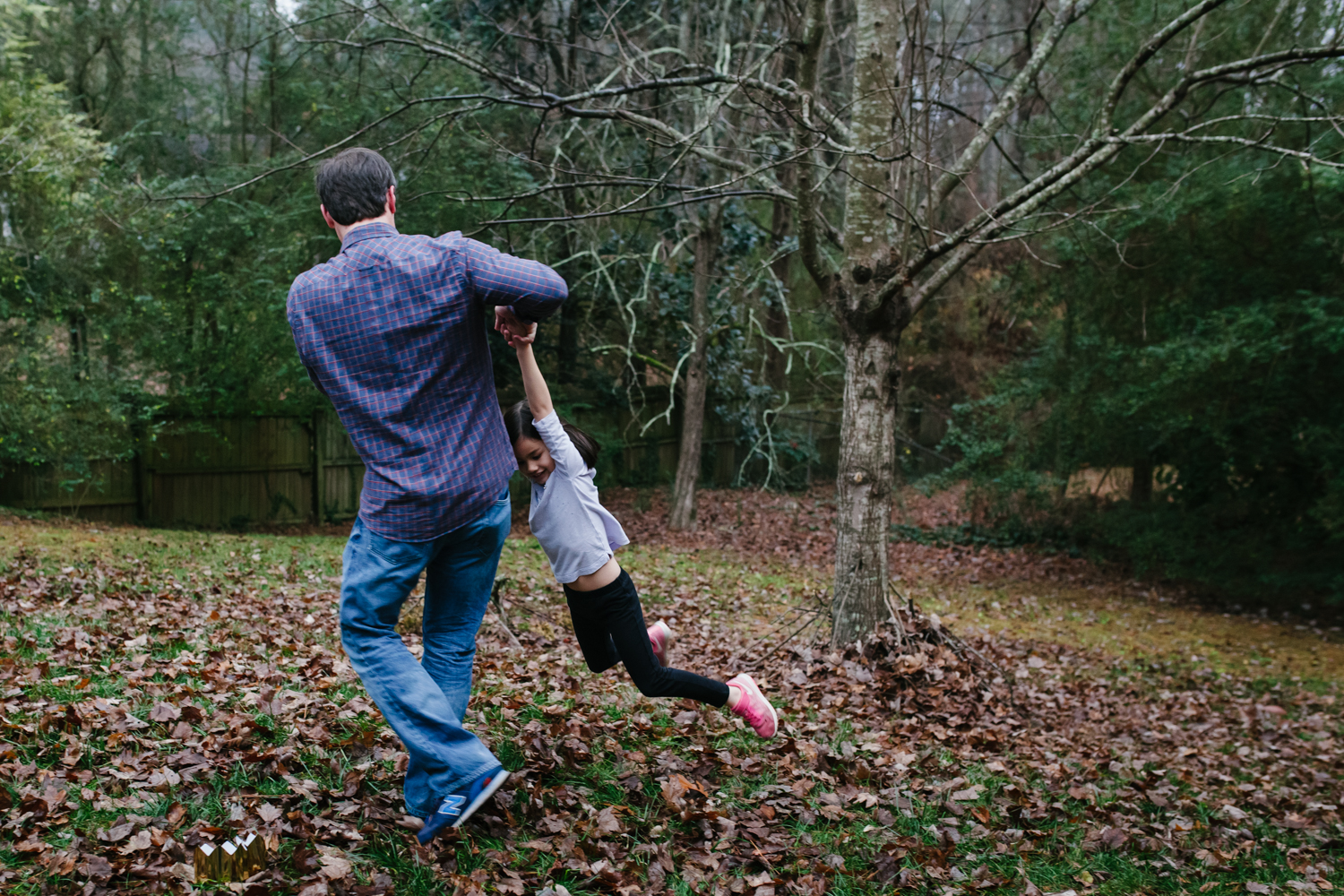 father swings daughter by the arms outside from family documentary photography session