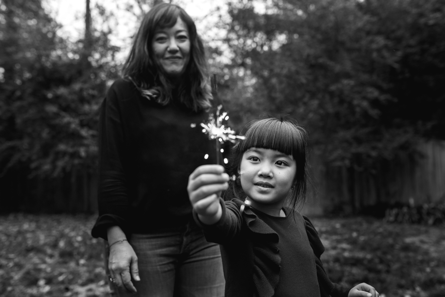 girl looks at a sparkler she is holding from a family documentary photography session in atlanta