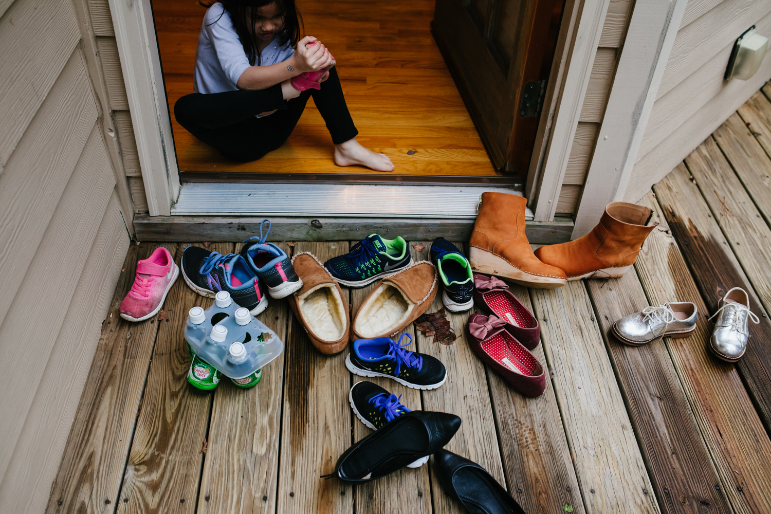 Girl takes off shoes with a pile of shoes by the door from family documentary photography session in atlanta