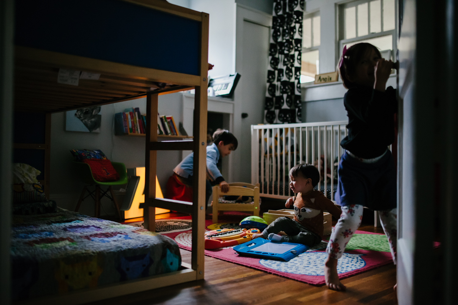 children playing in bedroom with moody light from family documentary photography session in atlanta